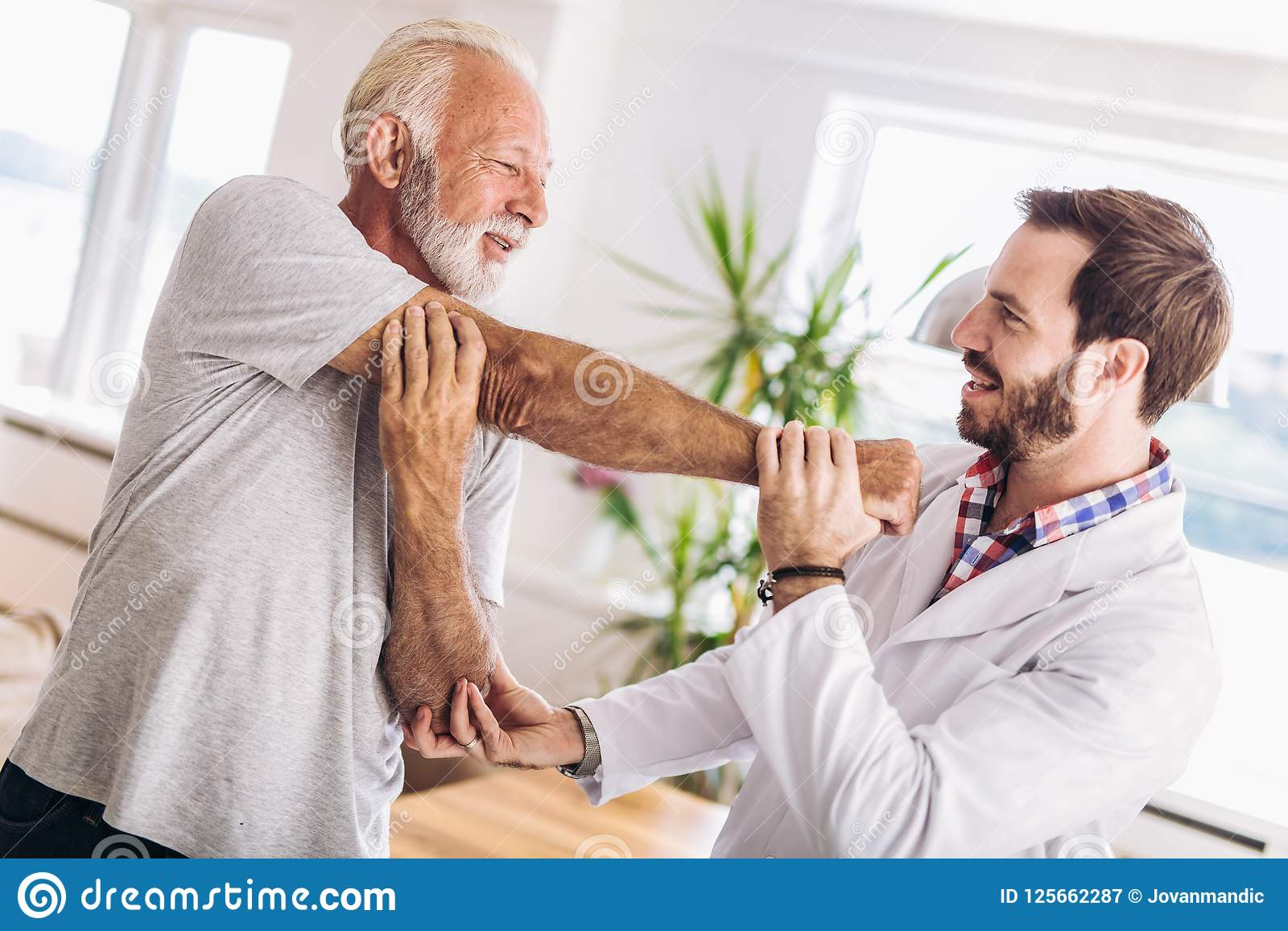 Male Chiropractor Doing Chiropractic Adjustment Of Female
