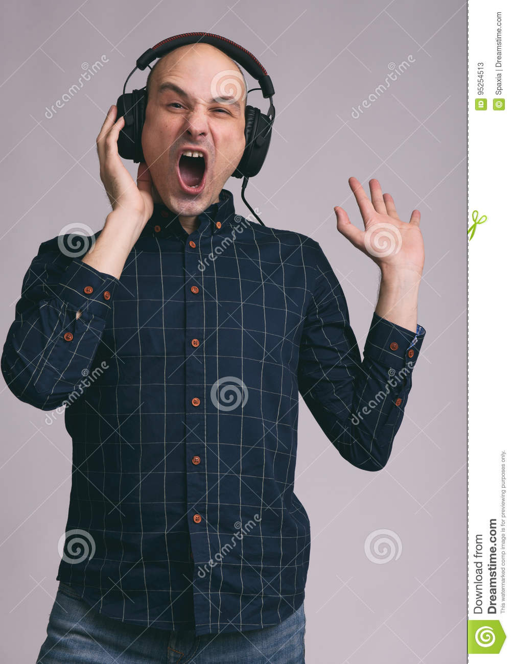 Funny man in headphones singing song. Isolated on gray