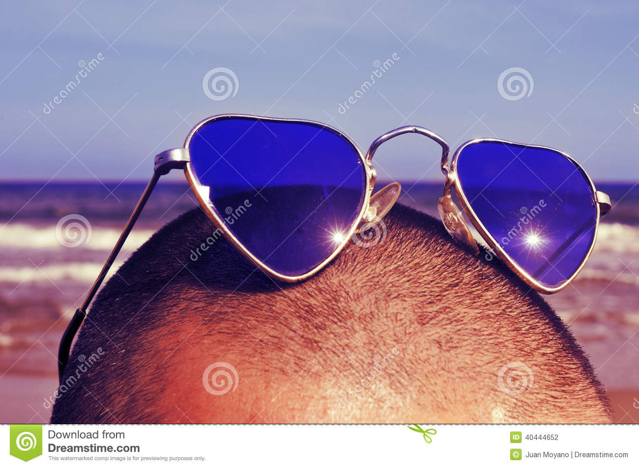 909667b93068 Closeup of the head of a man with heart-shaped sunglasses on the beach