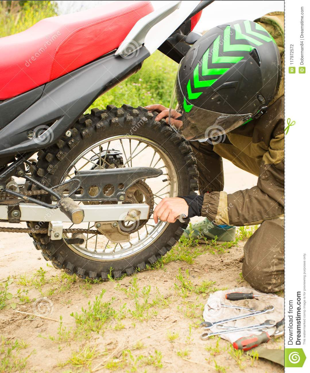 Man Adjusting Bolts With Socket Wrench On Rear Motorcycle