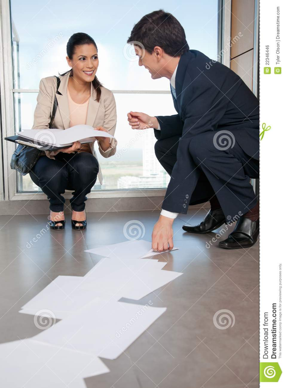 Man Helping Woman Collect Fallen Documents