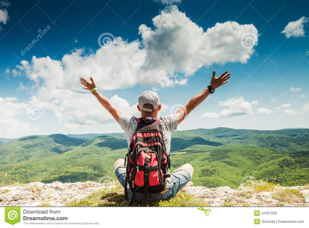 Man hiker greeting rich nature on the top of mountain
