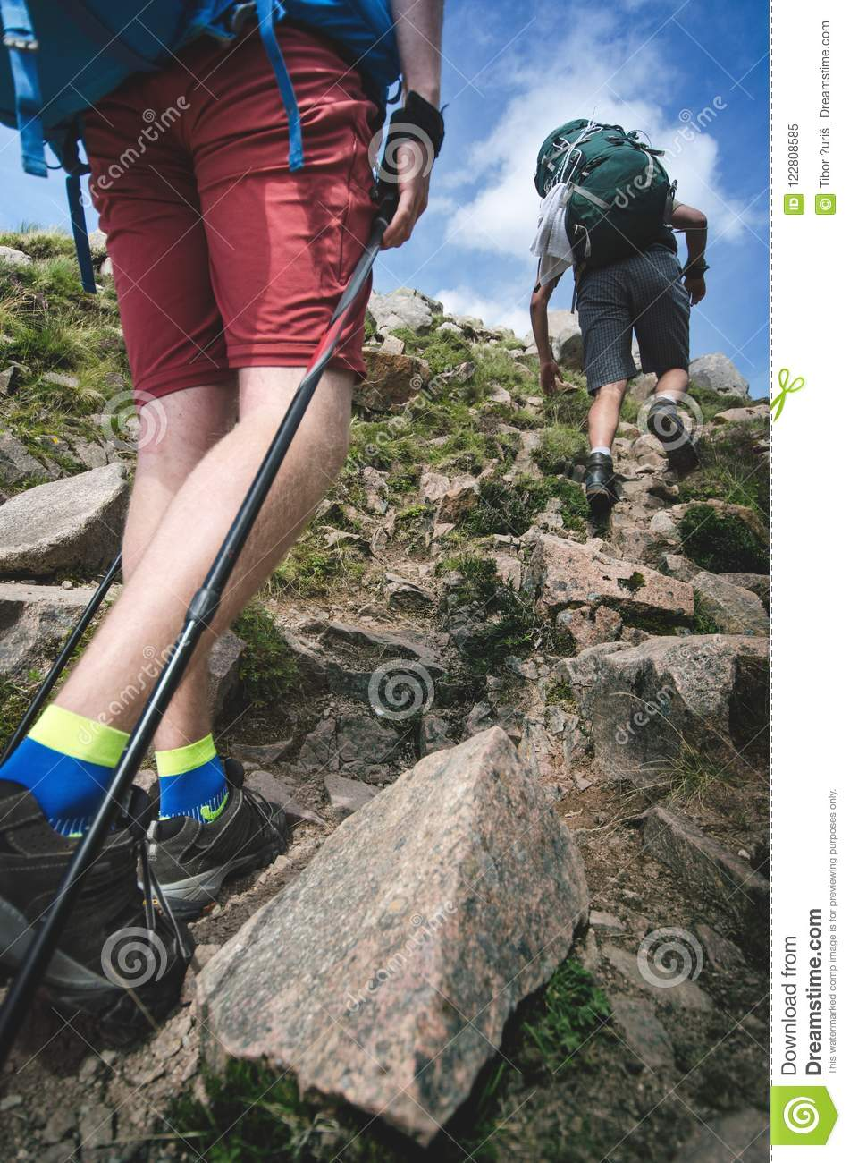 Man hiker walking on mountain rocks with sticks. Beautiful weather with Scotland nature. Detail of hiking boots on the difficult p