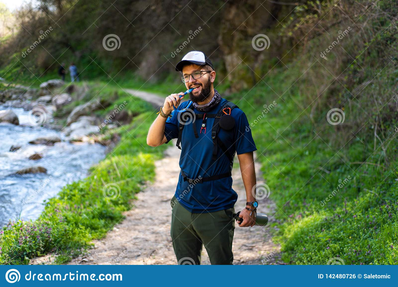 Man hiking and hydrating with water pipe
