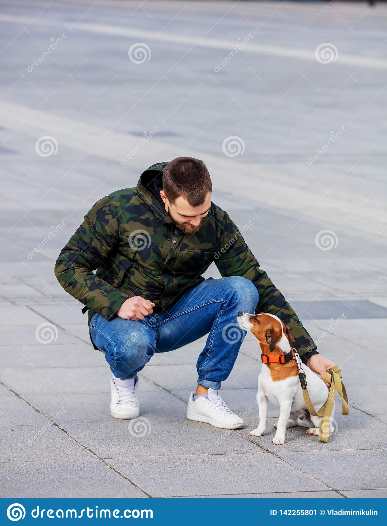 Man with his dog, Jack Russell Terrier, on the city street