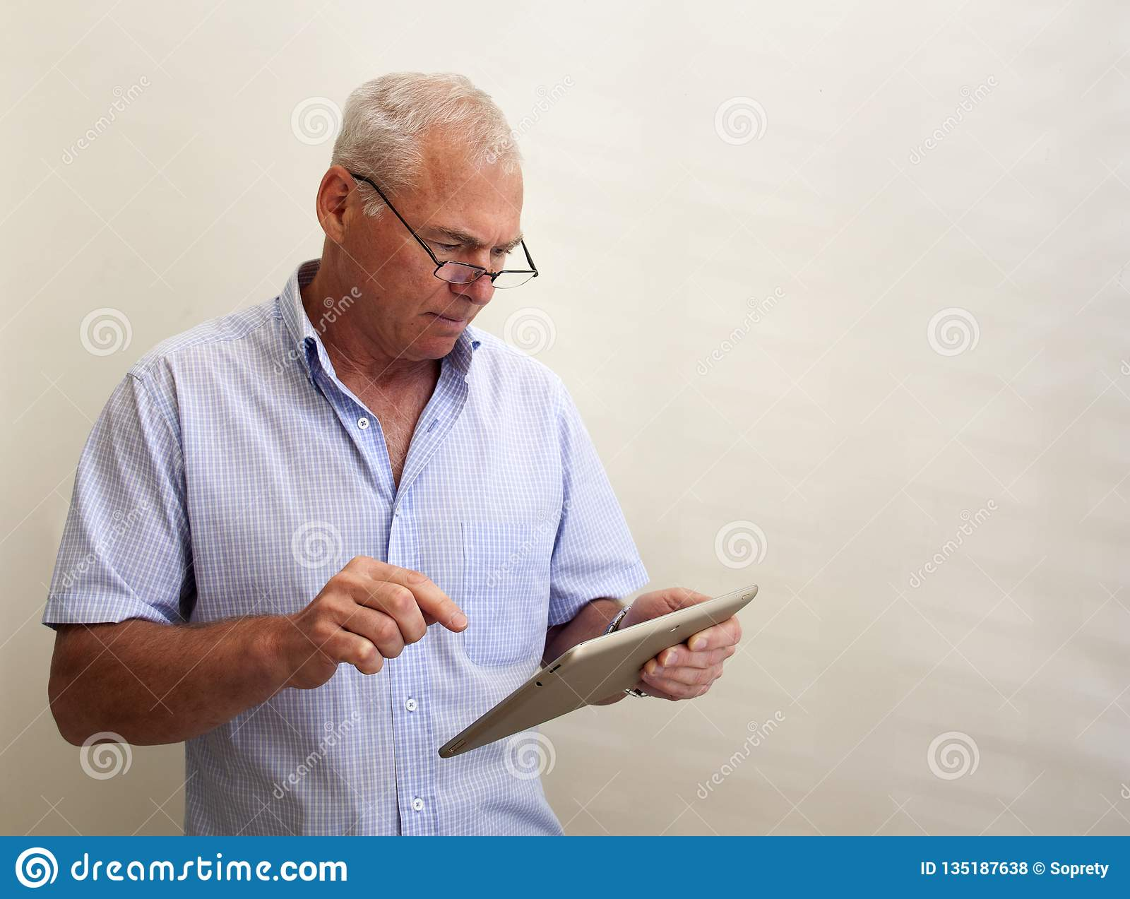 A man in his 60s with a pc tablet in his hand
