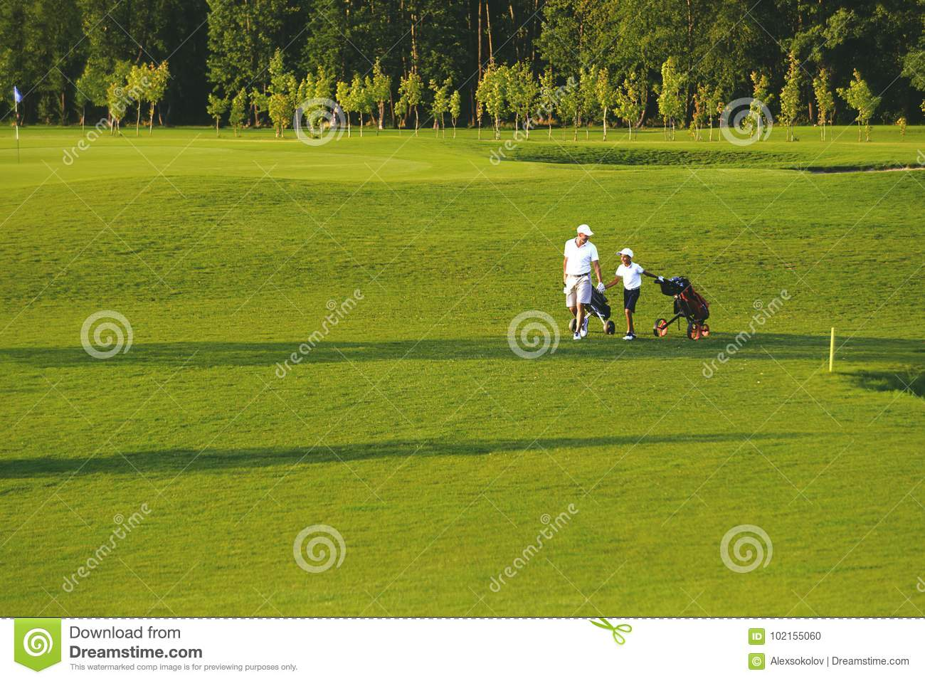 Man with his son golfers walking on golf course
