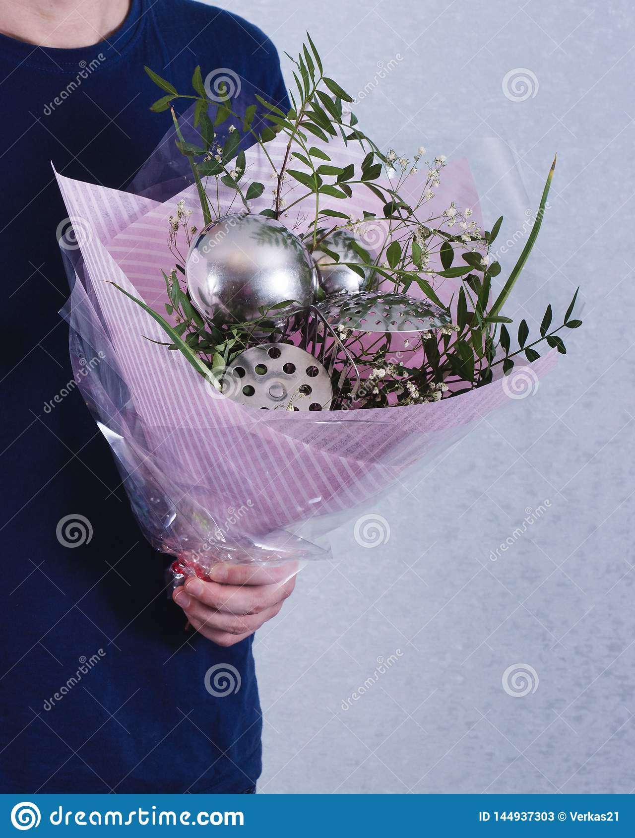 A man hold bouquet of flowers and ladles. concept of sexism, feminism and patriarchal society and gender inequality