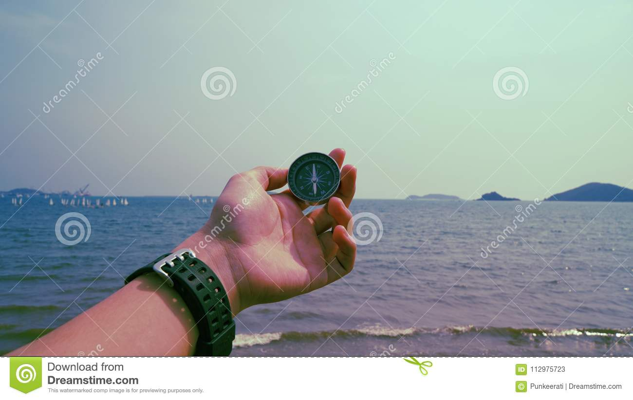 Man hold compass with sea and mountain at the background.