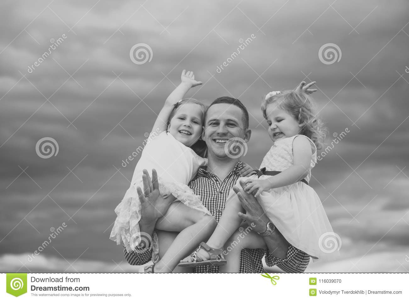 991b0c6254b8 Man hold girls on cloudy grey sky. Father and daughters happy smile on summer  day outdoors. Fathers day concept