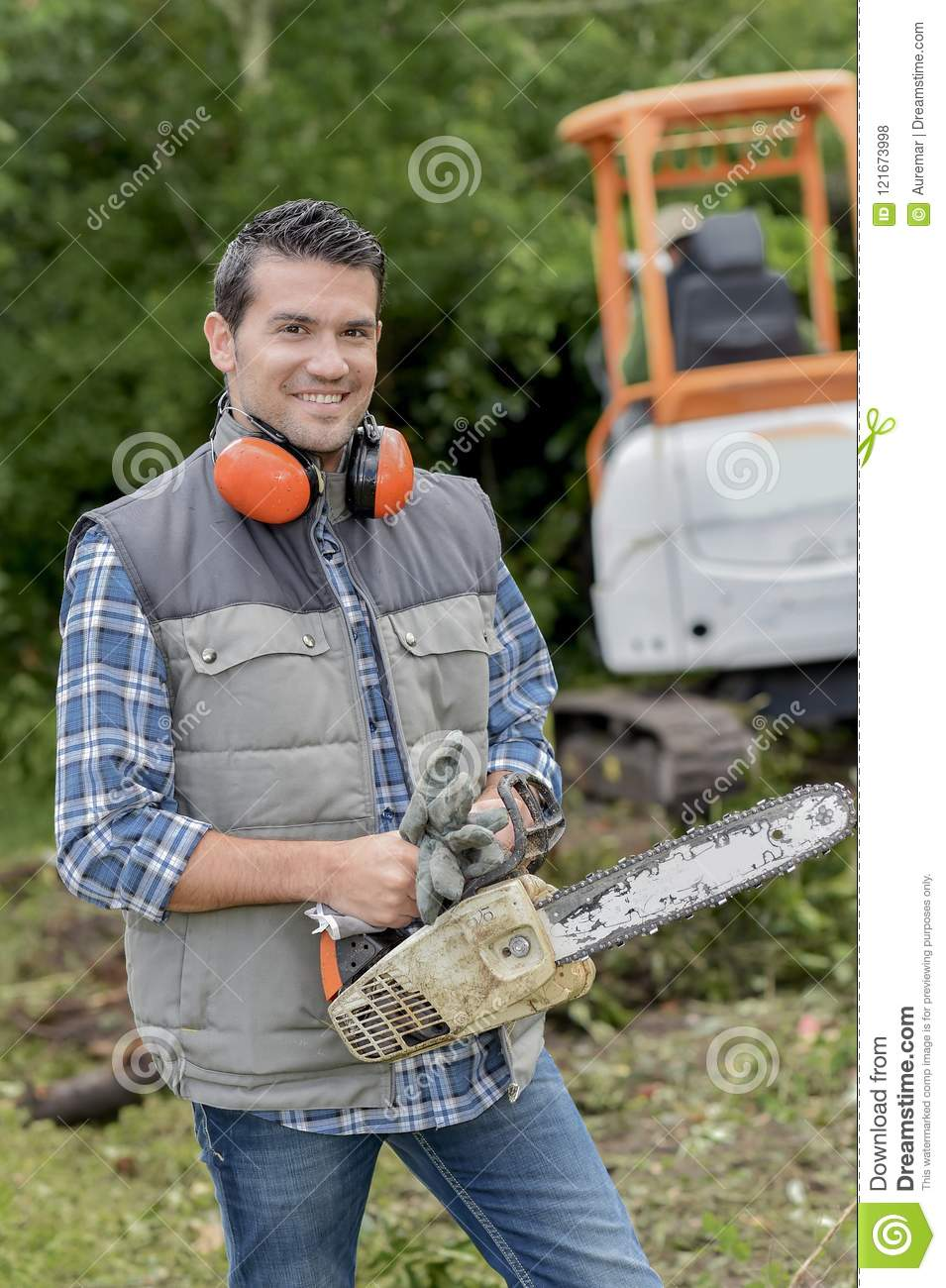 Man holding chainsaw wearing ear protectors