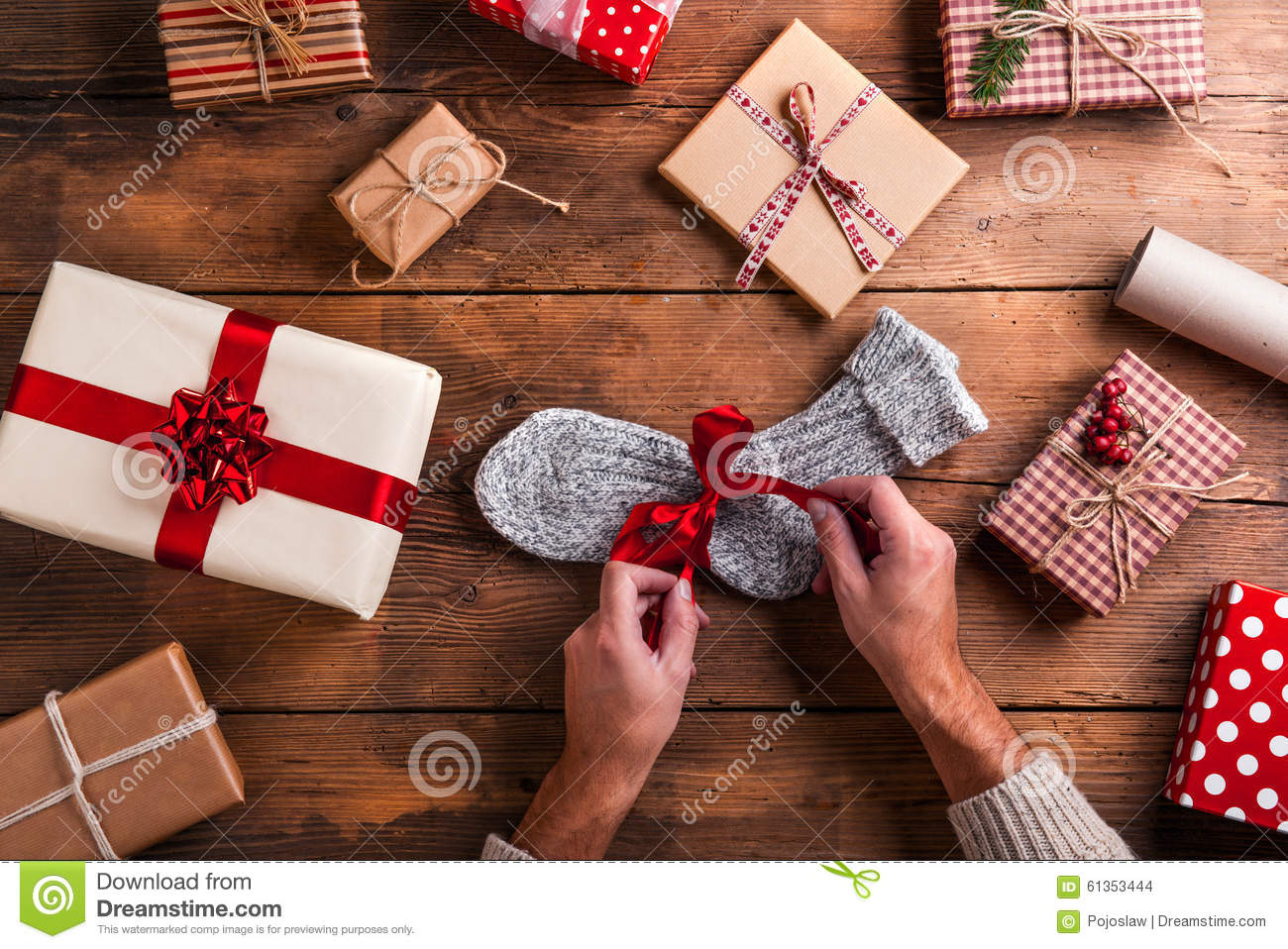 106da473da Man unwrapping Christmas present laid on a wooden table background