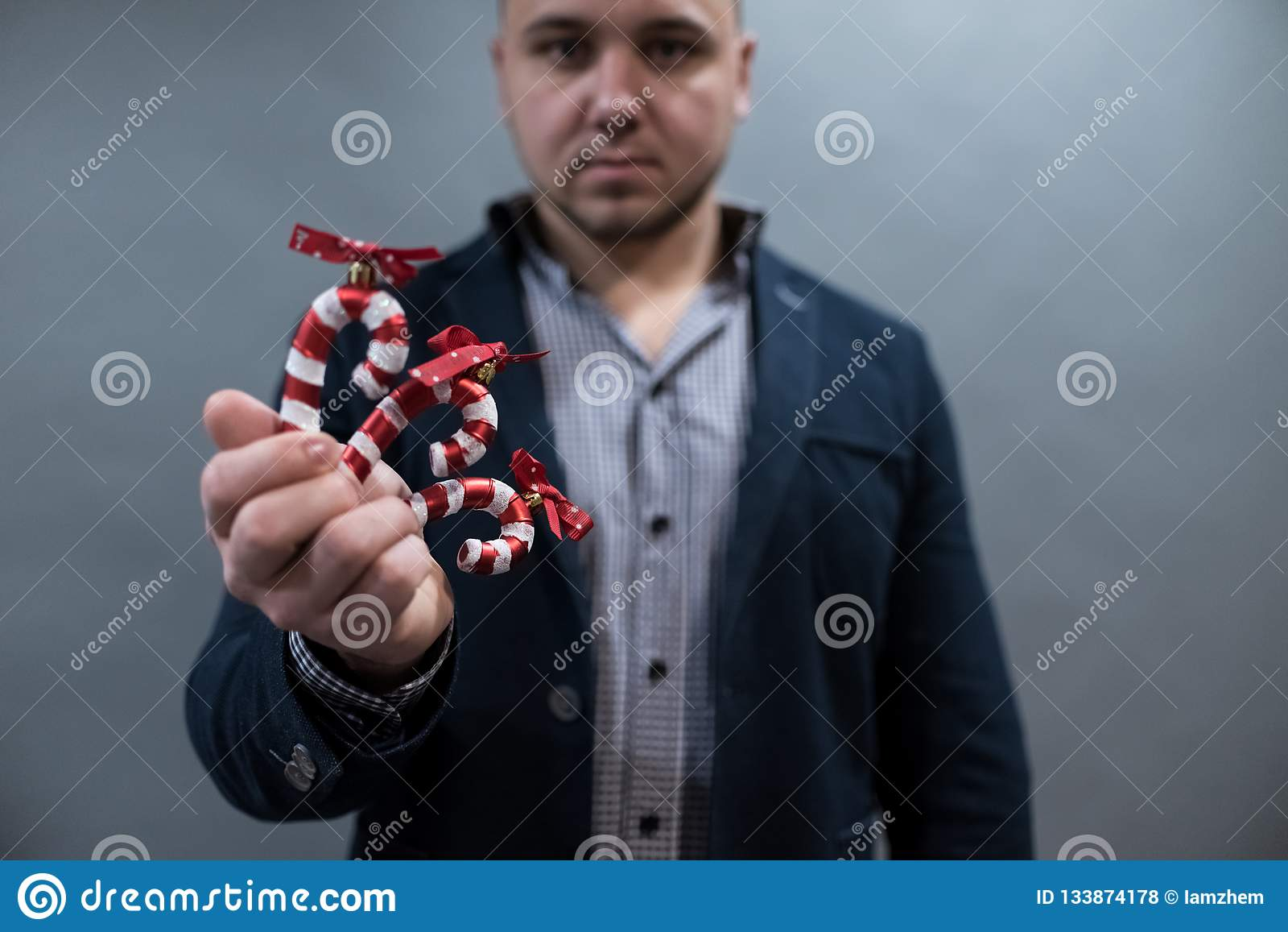 The man is holding a Christmas toy candy cane