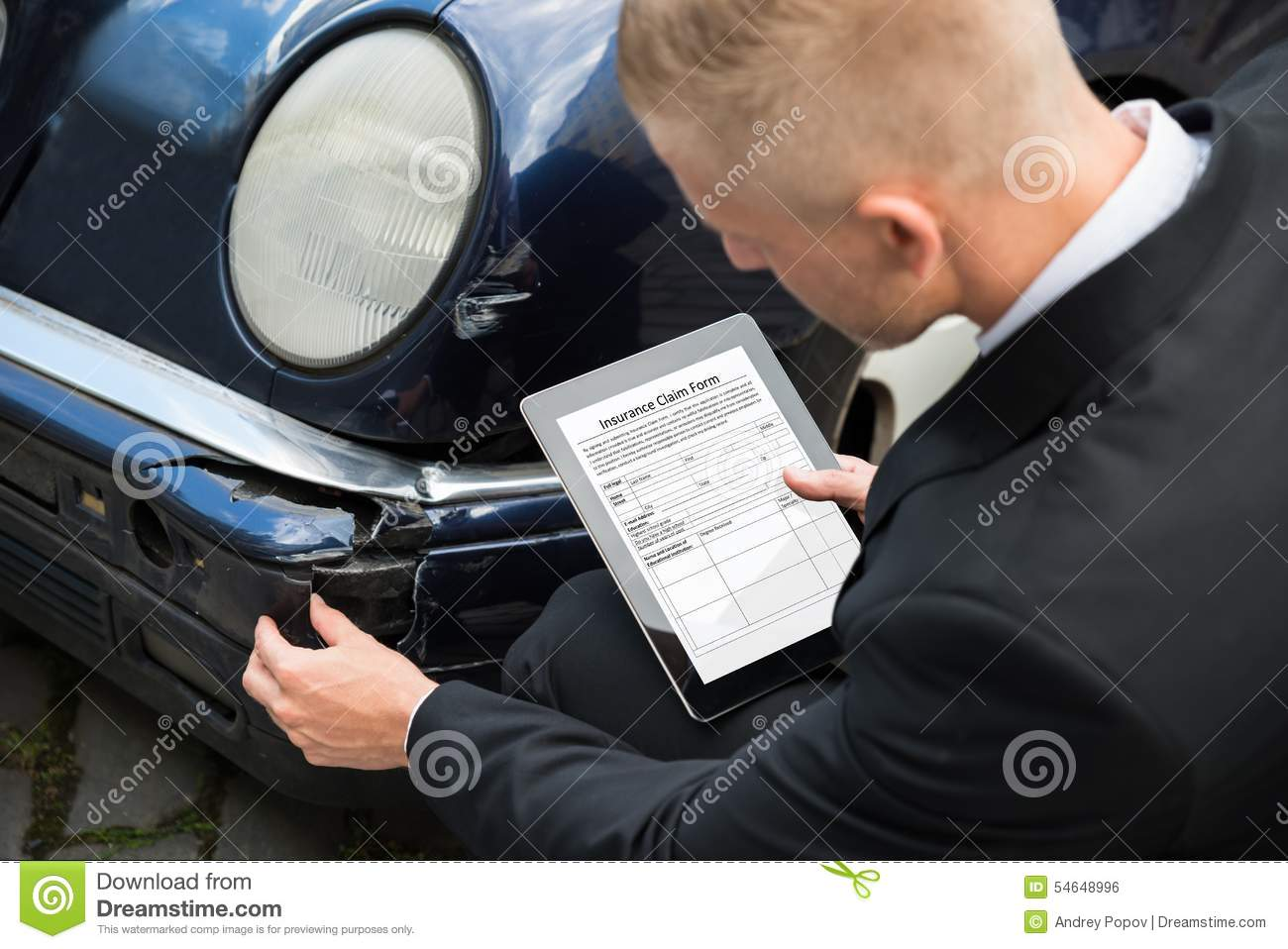 Man holding digital tablet examining damaged car