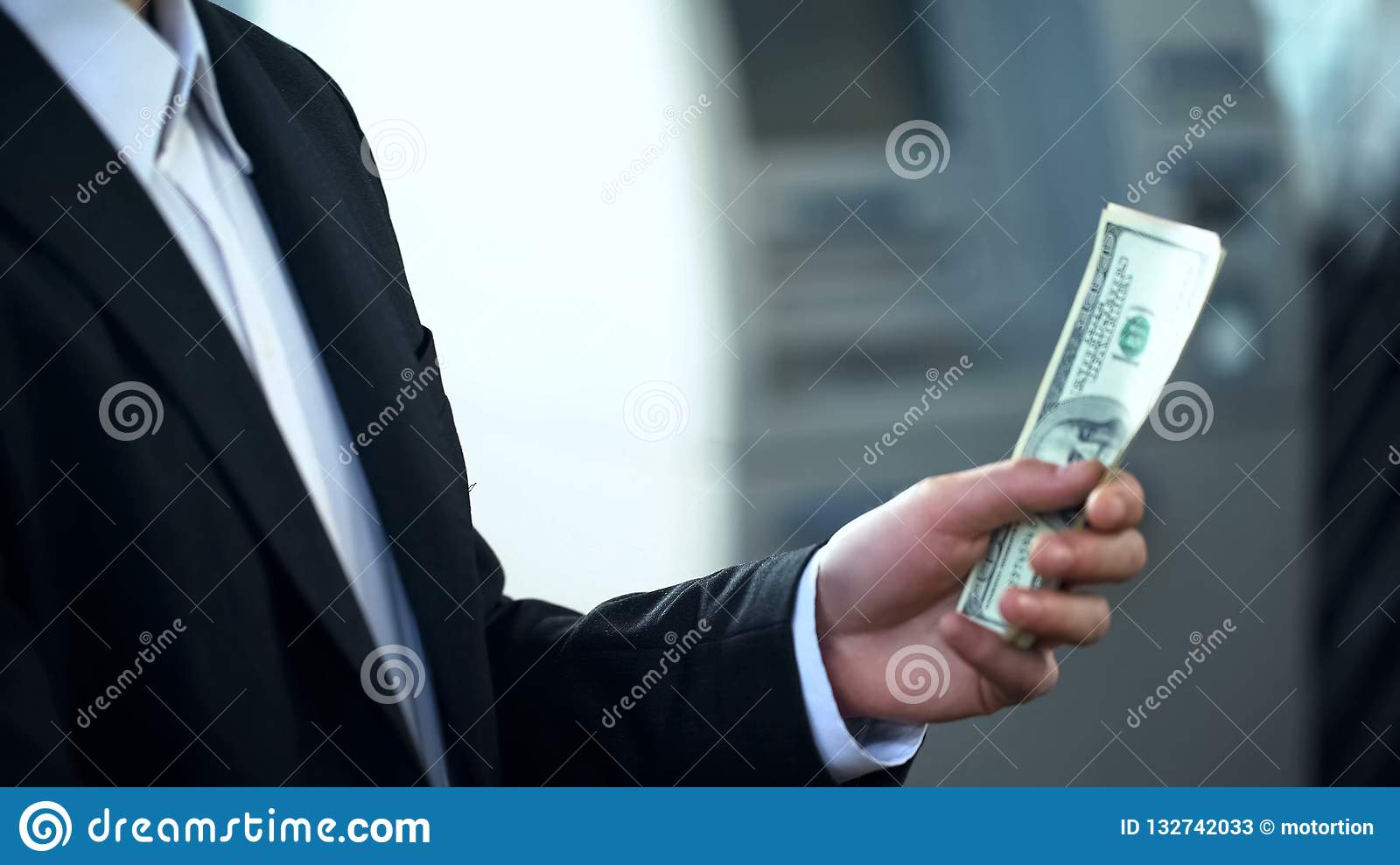 Man holding dollars banknotes withdrawn from ATM, good service, business trip