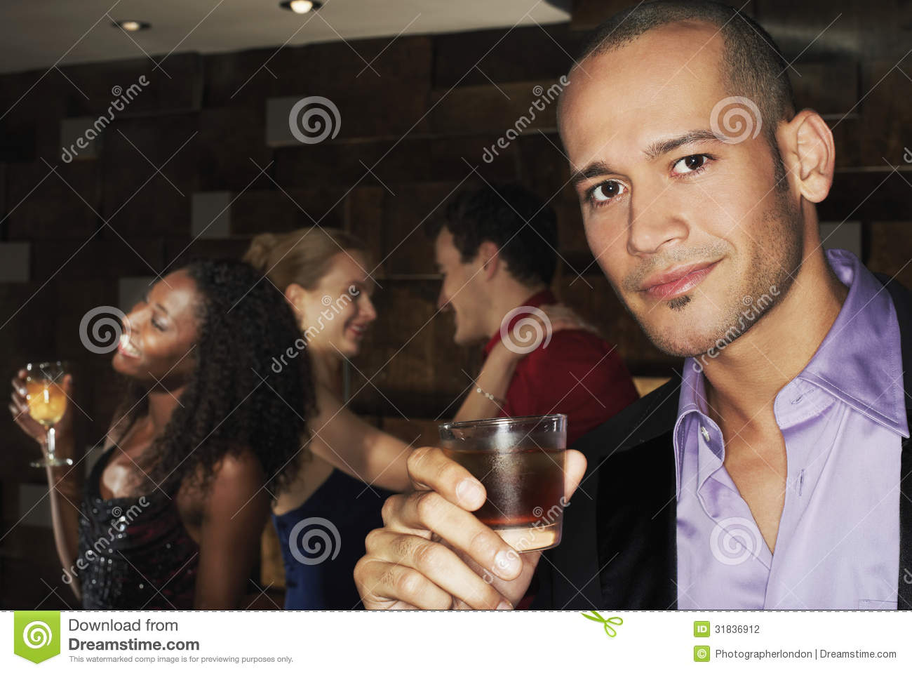 Man Holding Drink With People Dancing Behind At Bar Stock