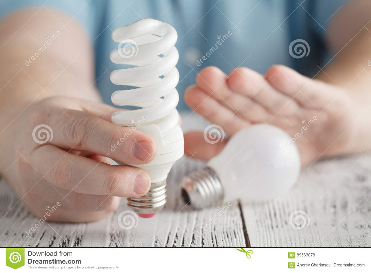 Man Holding An Energy Saving Lamp And Refuse Normal Light Bulb Royalty Free Stock Image