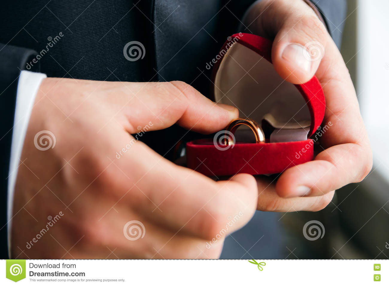 Man Holding Engagement Ring In Box Close Up