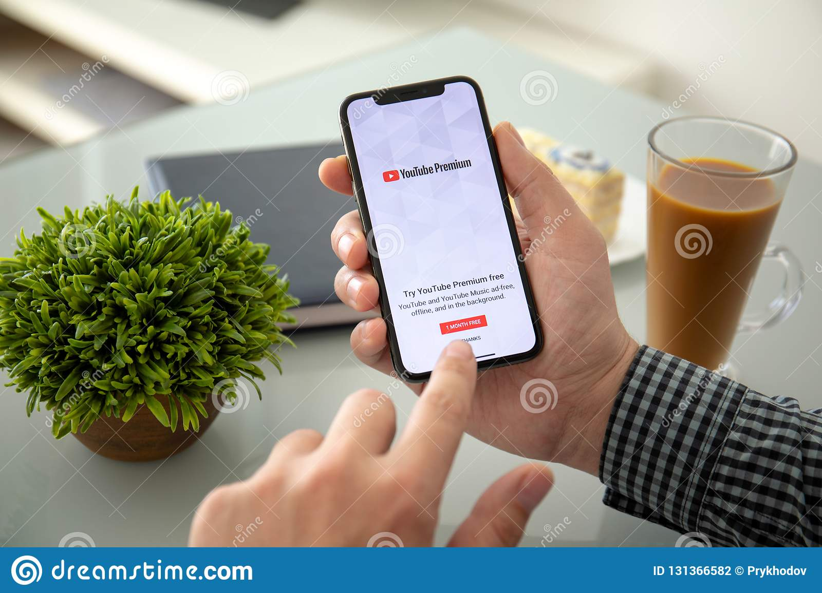 Man holding iPhone X with app YouTube Premium on screen