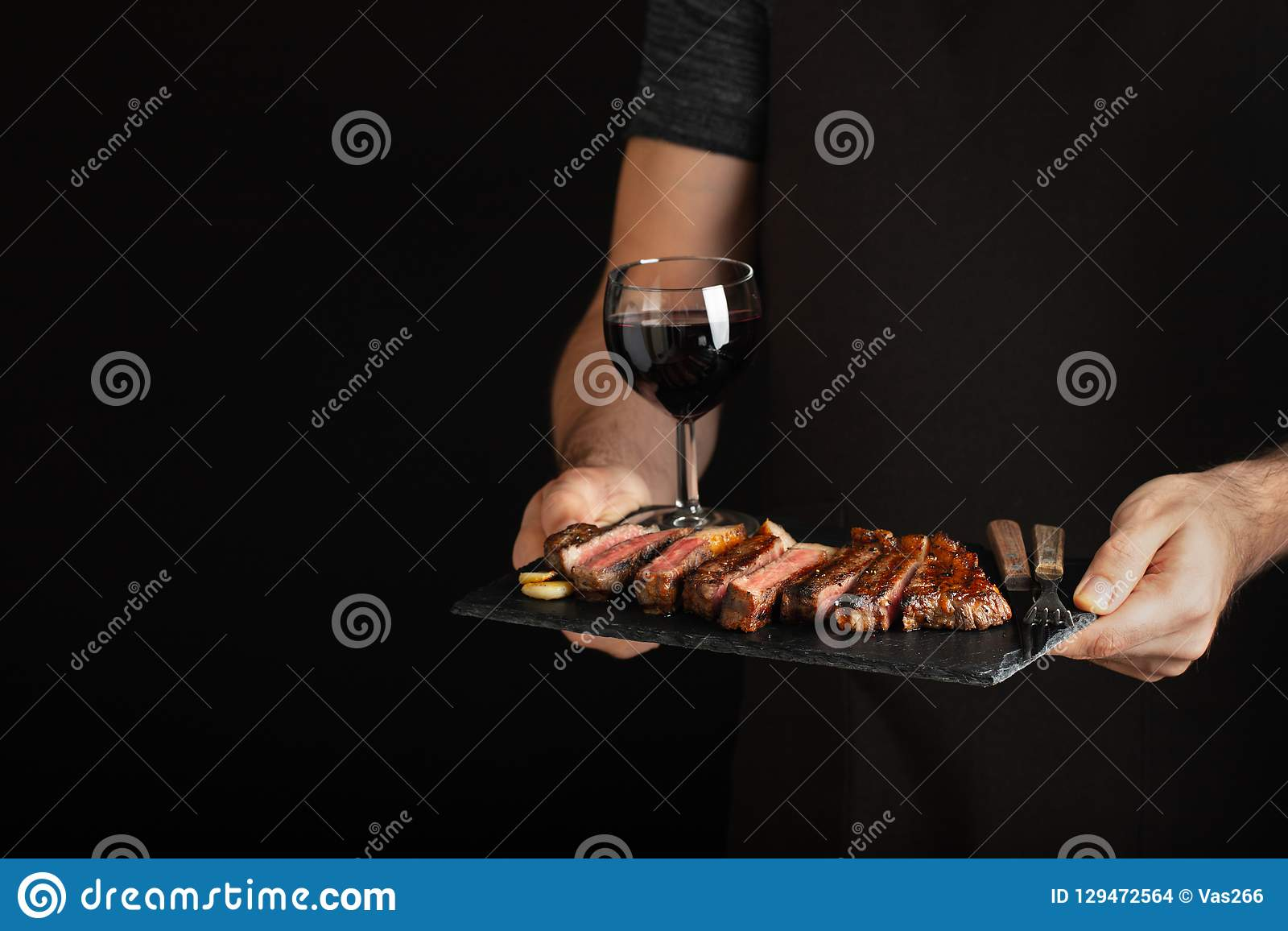 Man holding juicy grilled beef steak with spices and red wine glass on a stone cutting board on a black background. With