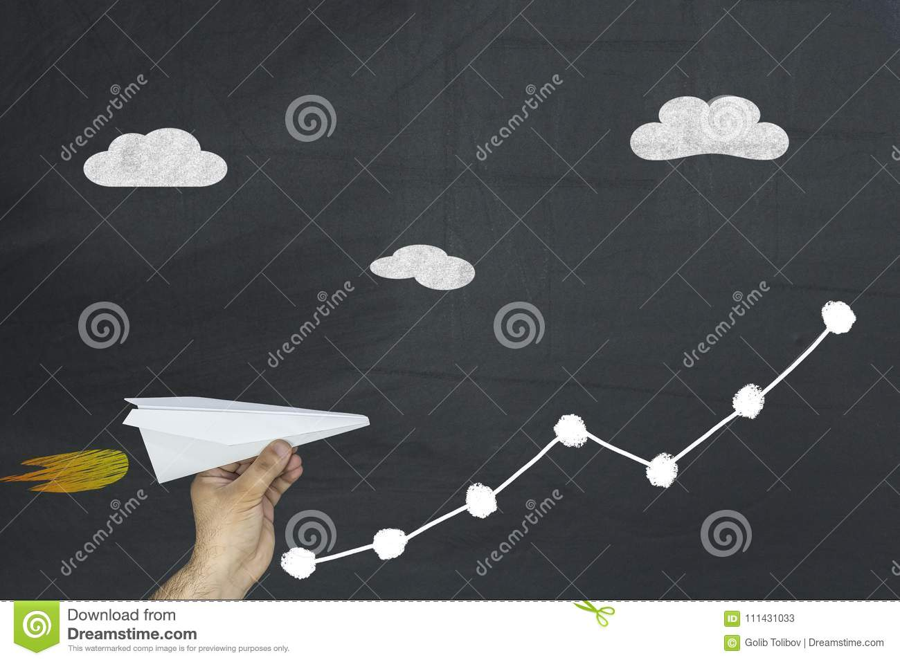 Man holding paper plane flying up on growing graph arrow chart on chalkboard. Business finance concept.