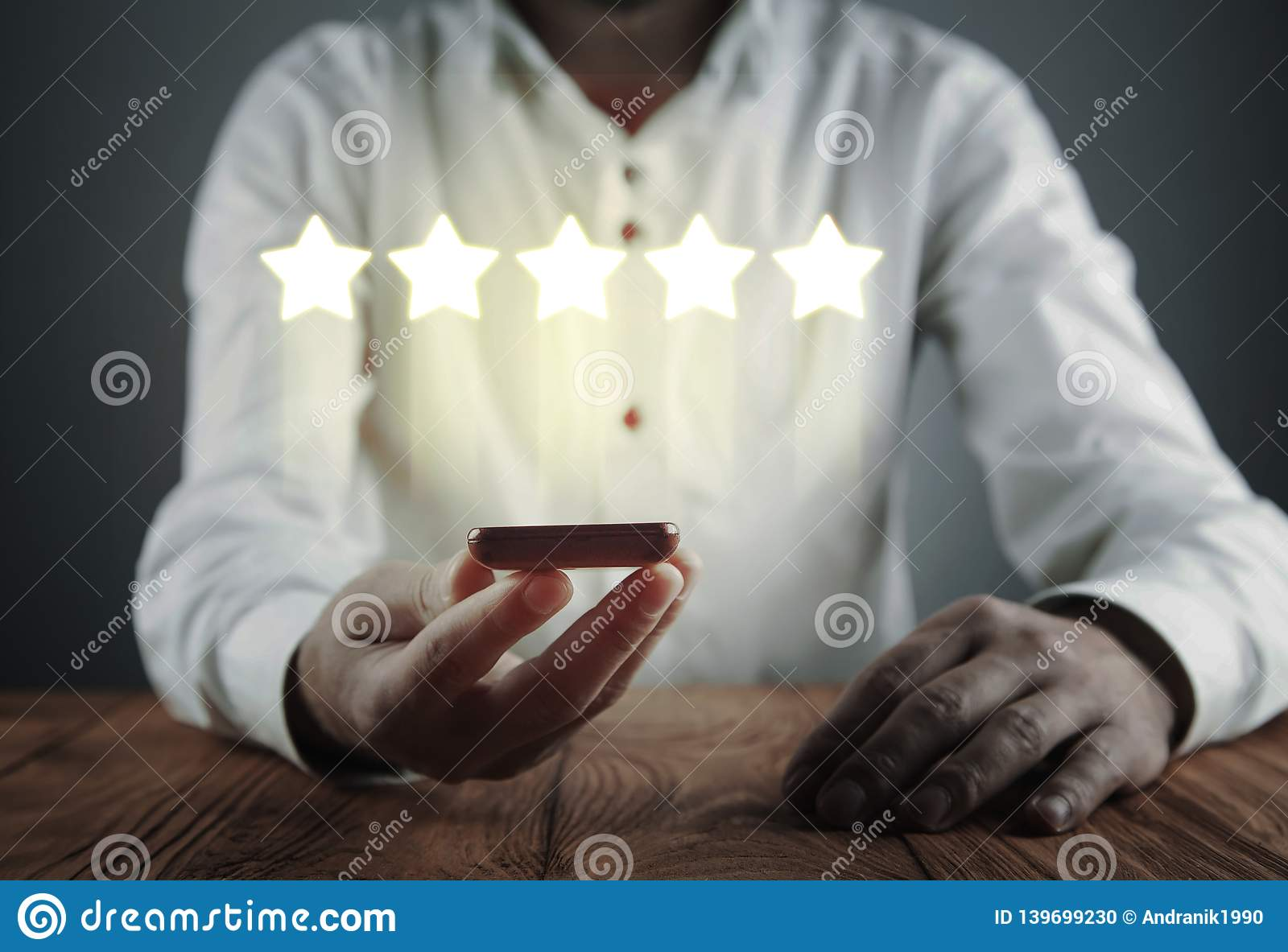 Man holding phone with five stars. Increase rating