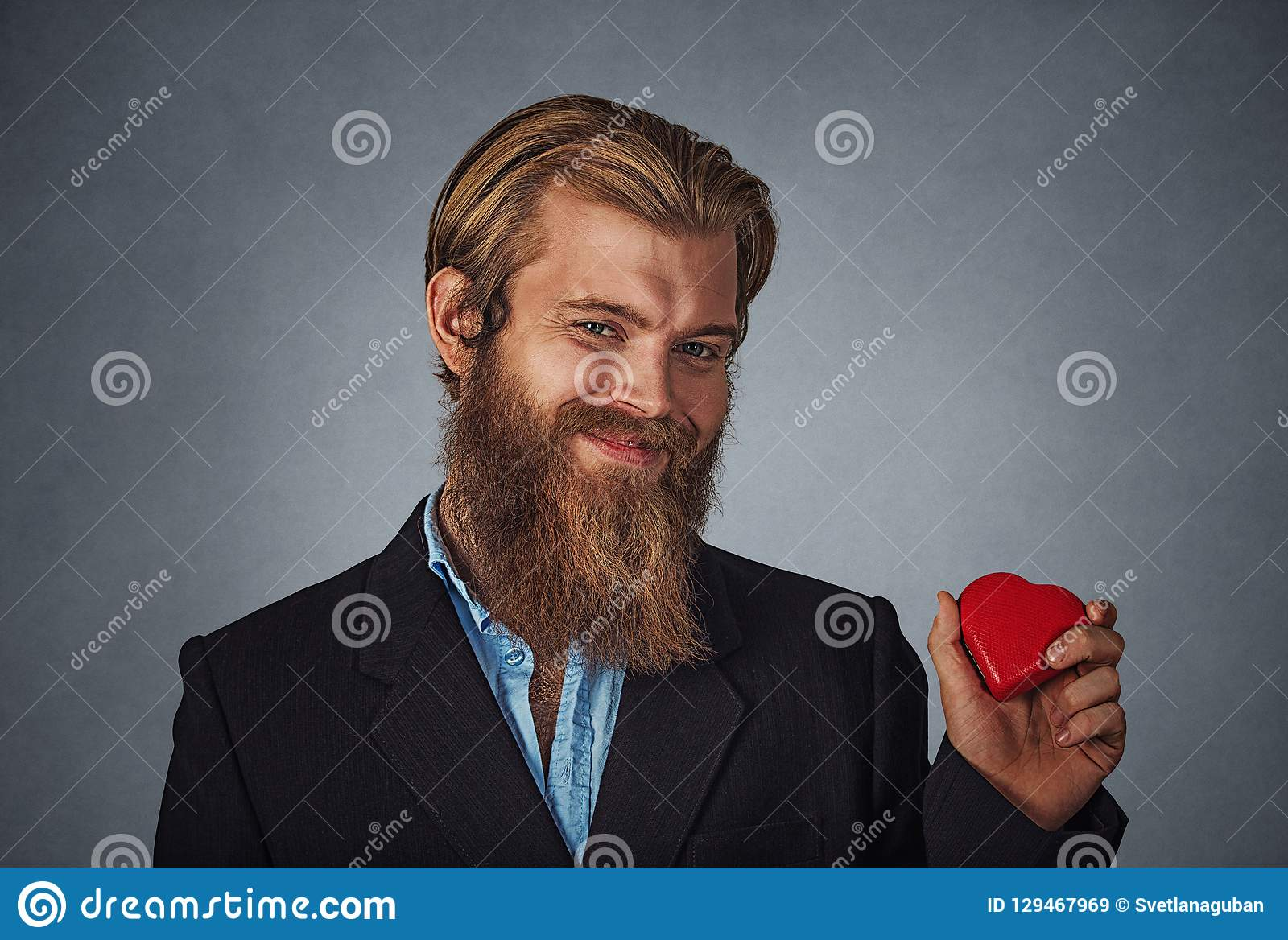 d40e2810a75 ... holding red heart shaped gift box ready for Valentine`s day. Isolated  on gray grey studio wall Background. Negative face expression