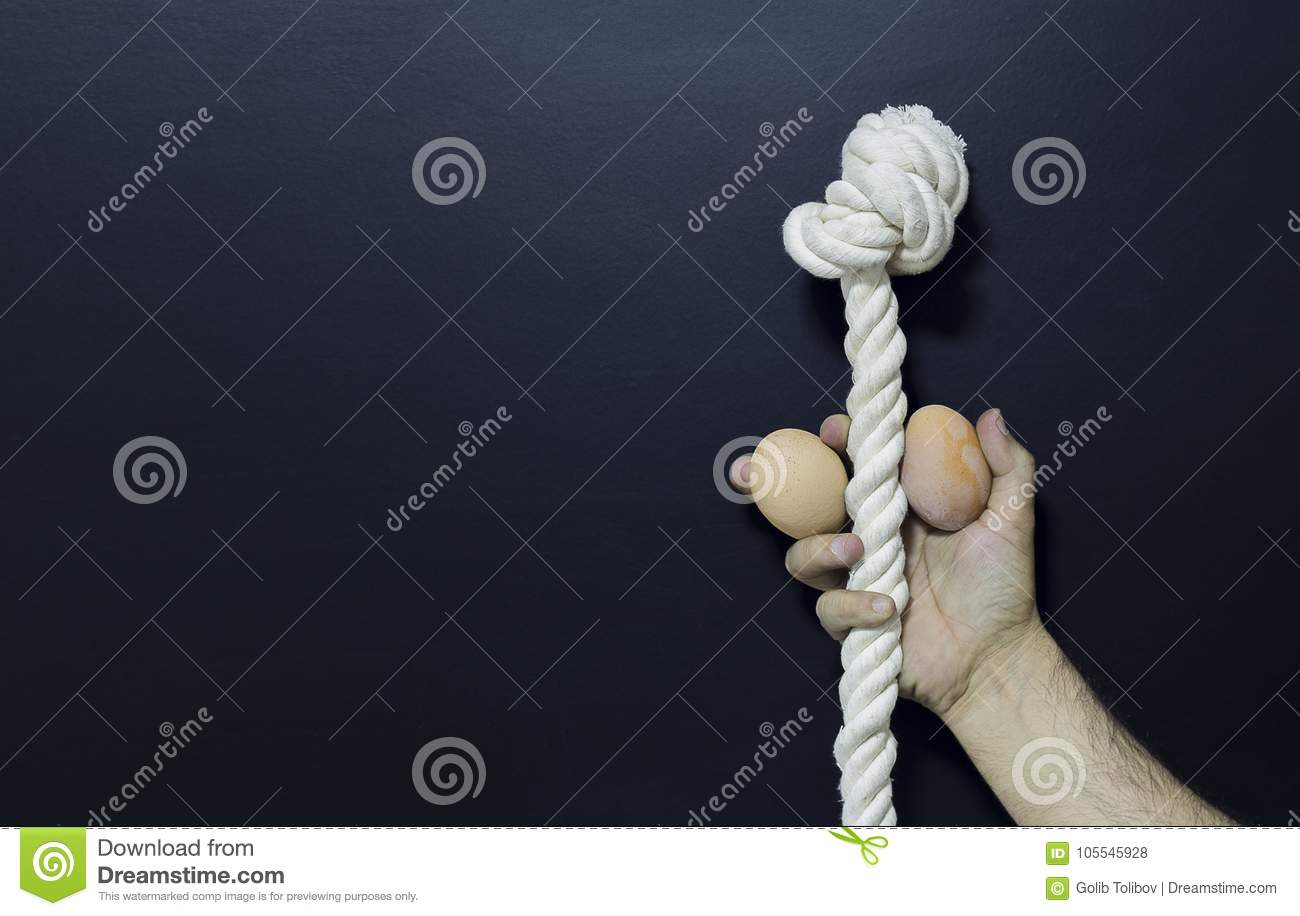 Man holding rope and two eggs as symbol of male penis
