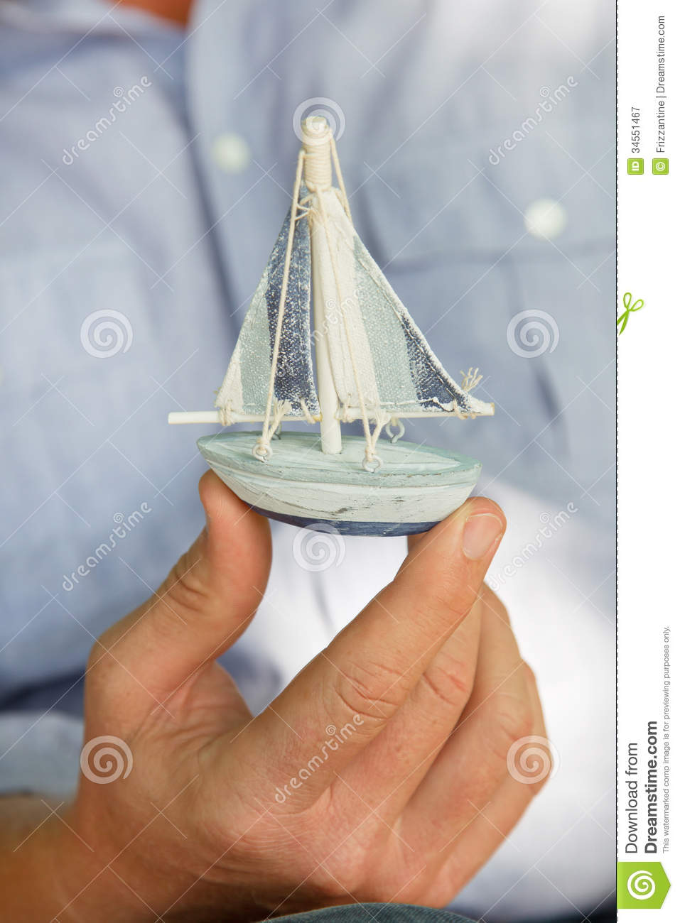 Man Holding A Small Toy Sailing Boat Concept For Sailing