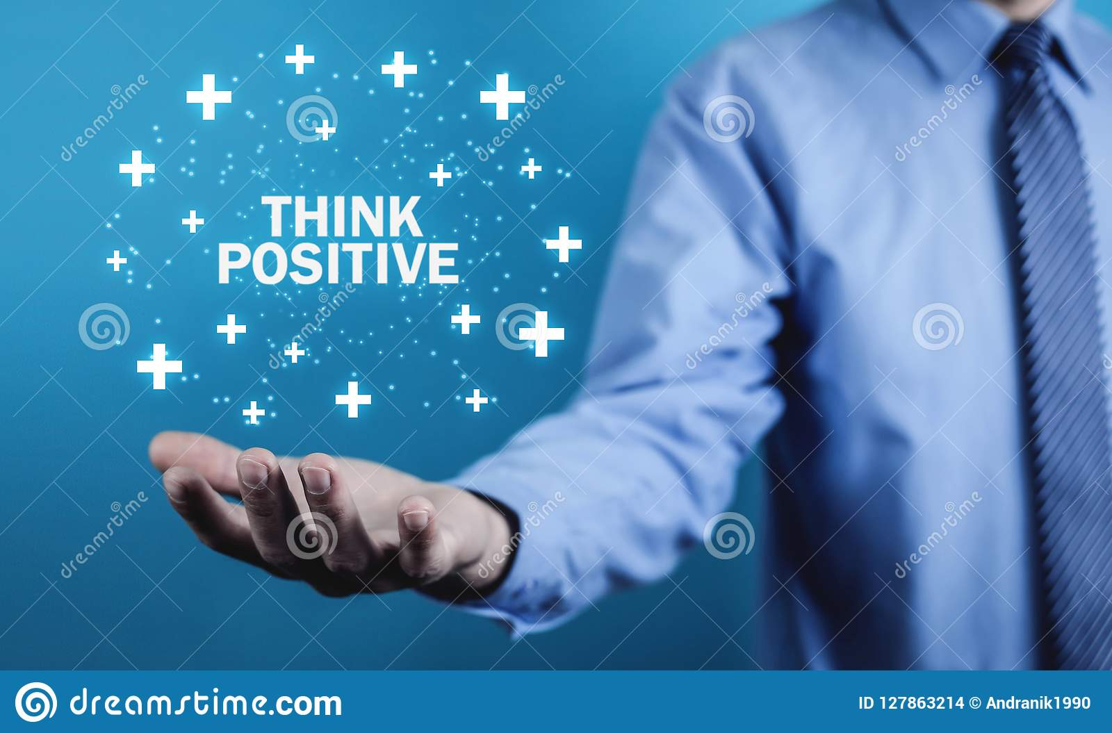 Man holding Think Positive words with plus signs.