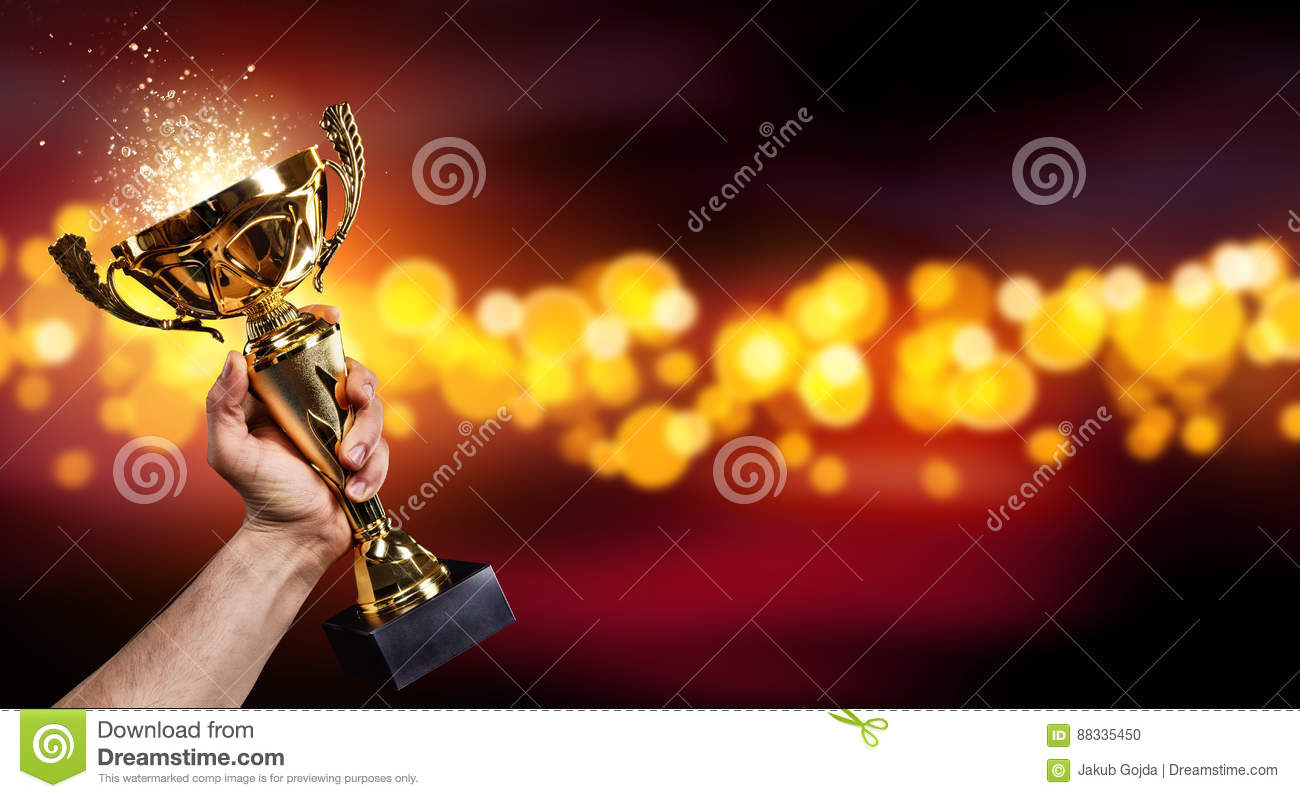 Man holding up a gold trophy cup