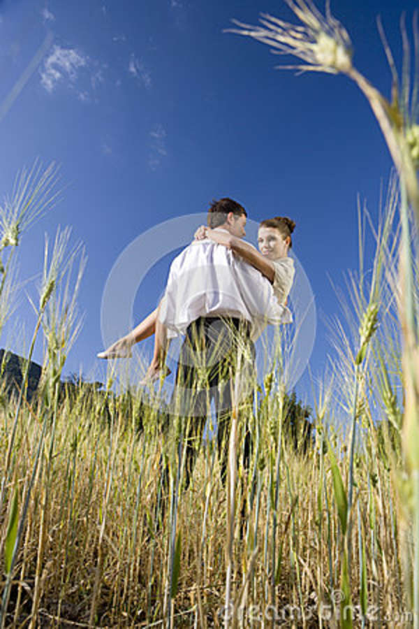 Man holding woman in rural field