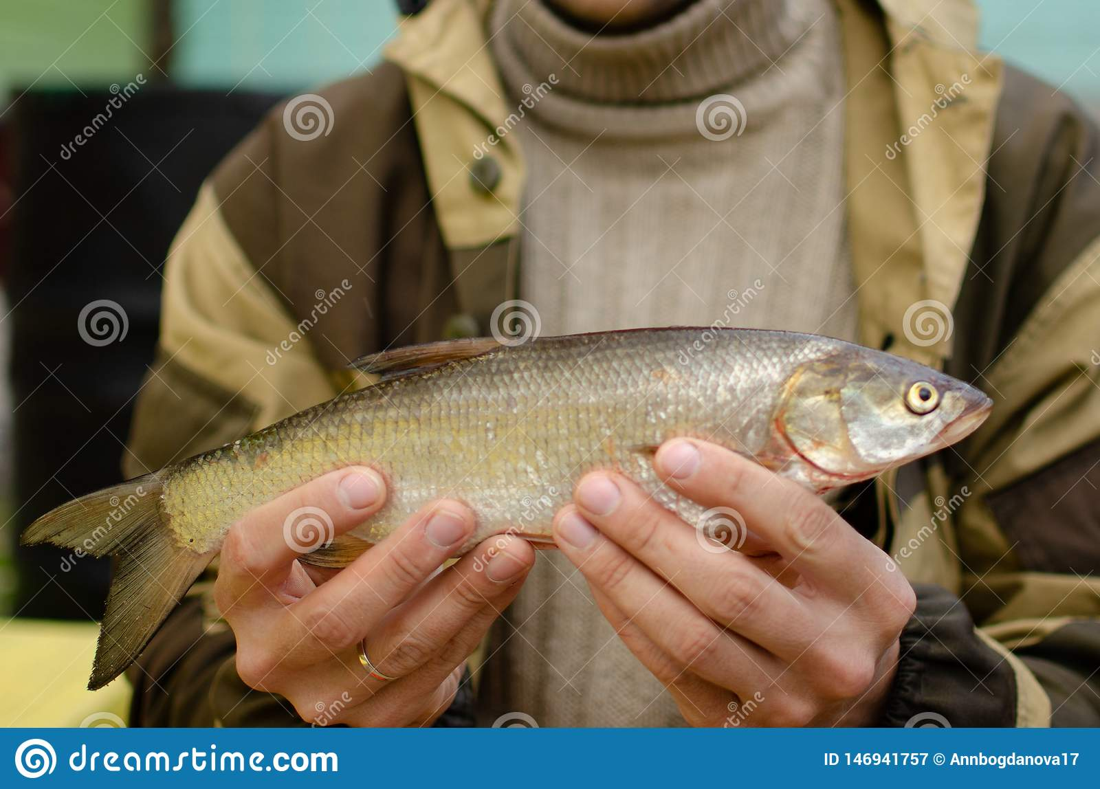 Man holds caught fish in his hands.