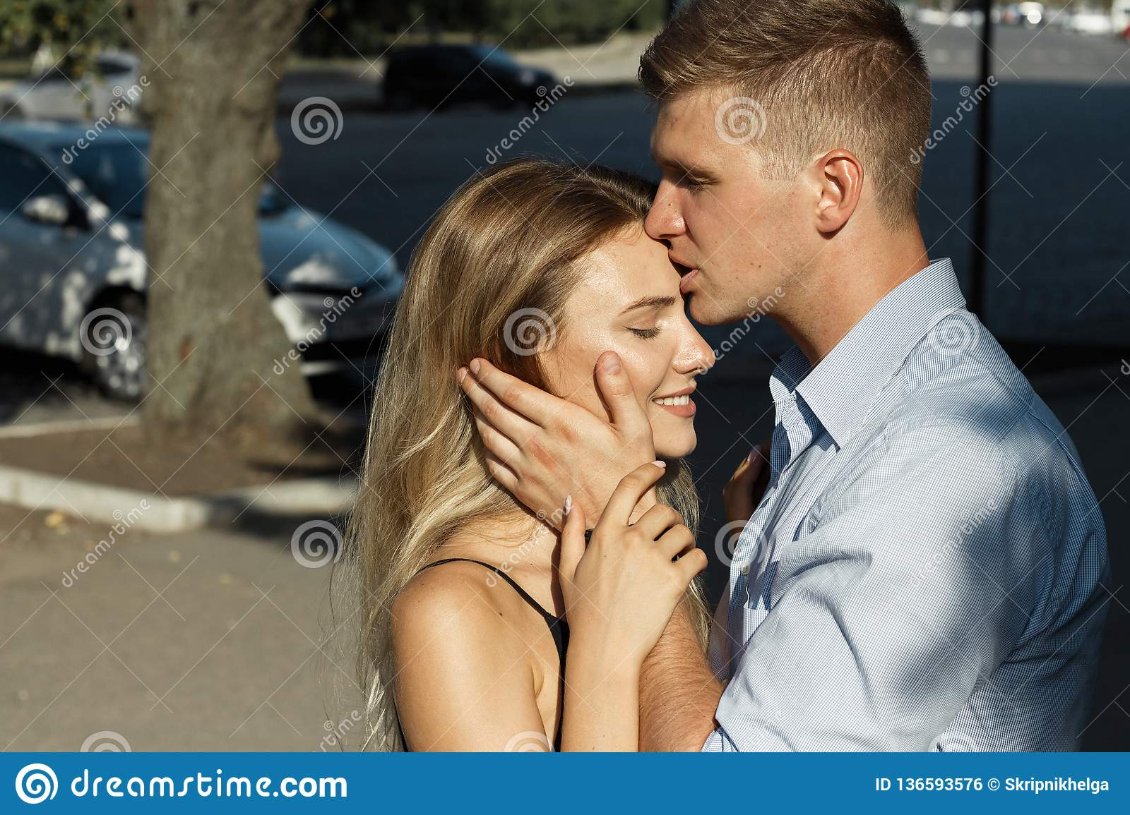 Man Holds Girl For Head And Kisses On Forehead, Close-up