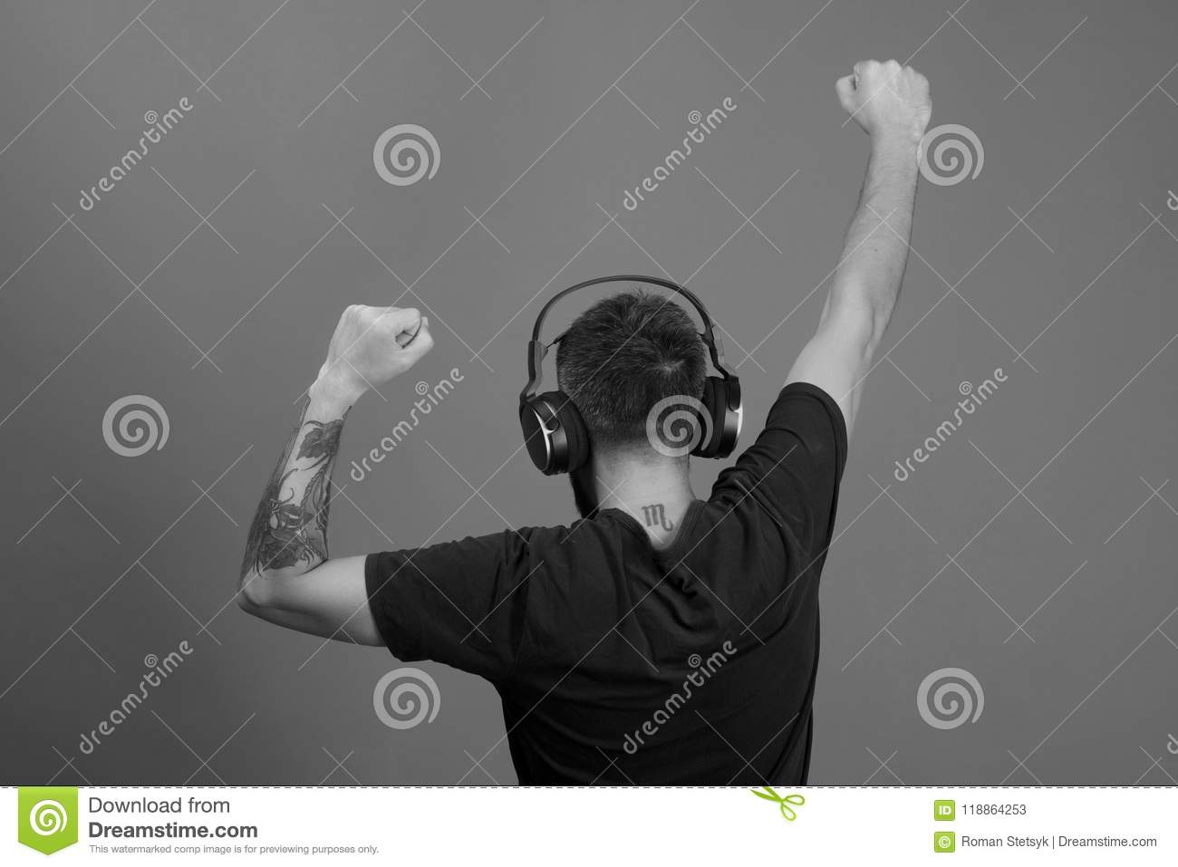 Man holds hands up dancing on blue background. Relax and music concept. Dj with scorpio tattoo wears headphones