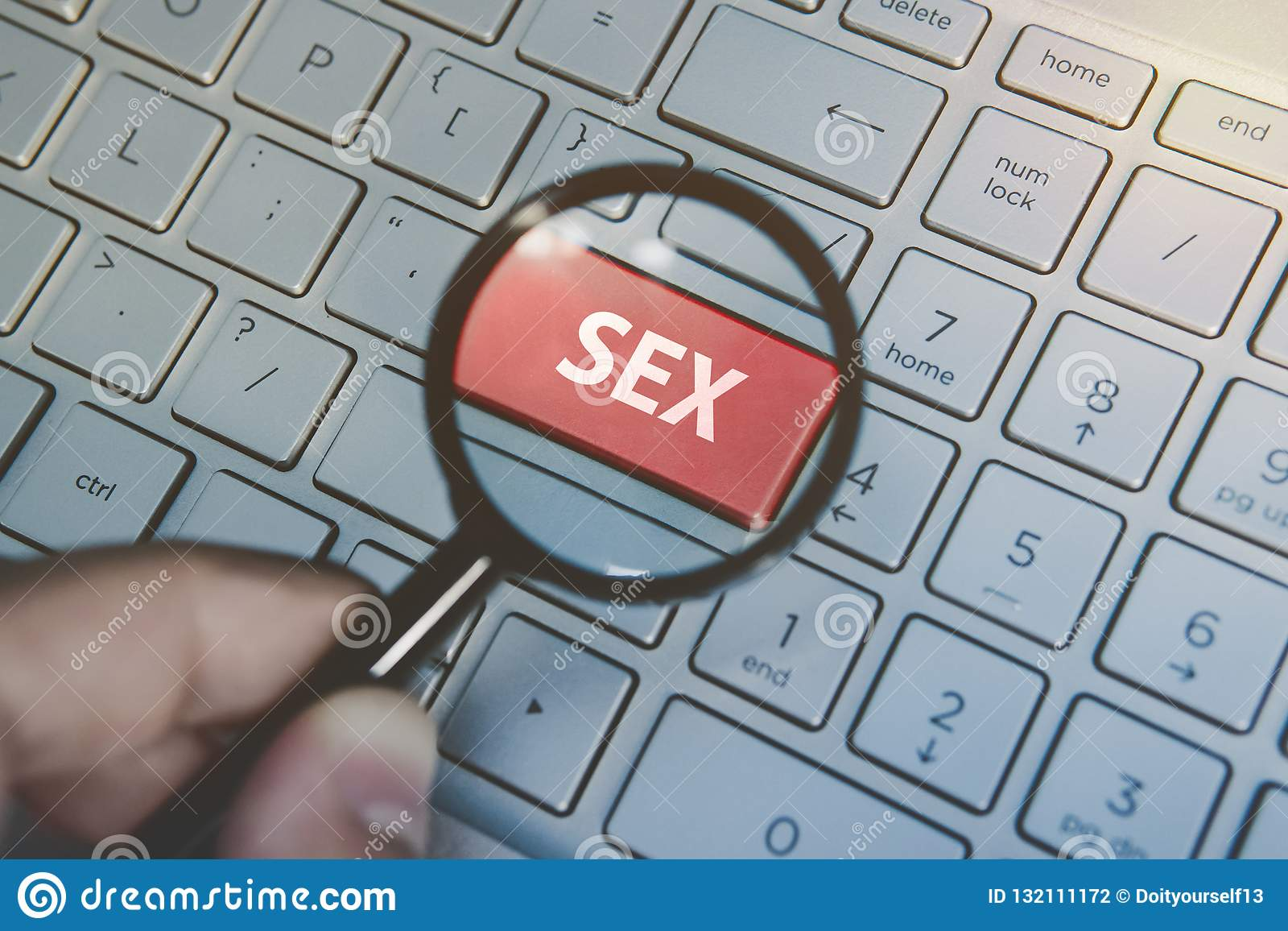 Man holds magnifying glass above the enter red key with the written word Sex on the computer keyboard background