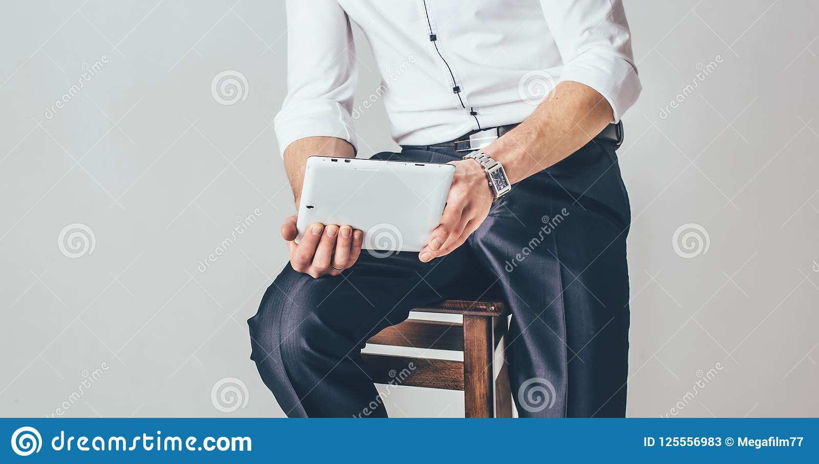 The man holds a tablet in his hands on the white background. He sits on a chair dressed in a swanky white shirt and pants