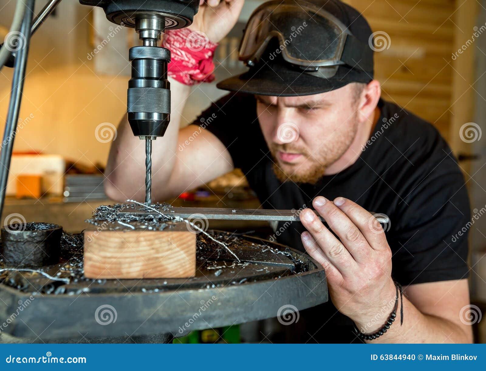 Man i arbete på press för elektrisk drillborr