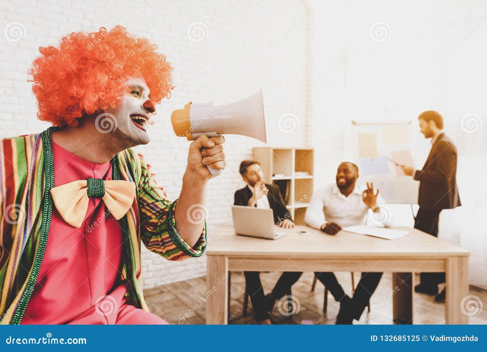 Man i clownen Costume med högtalaren i regeringsställning
