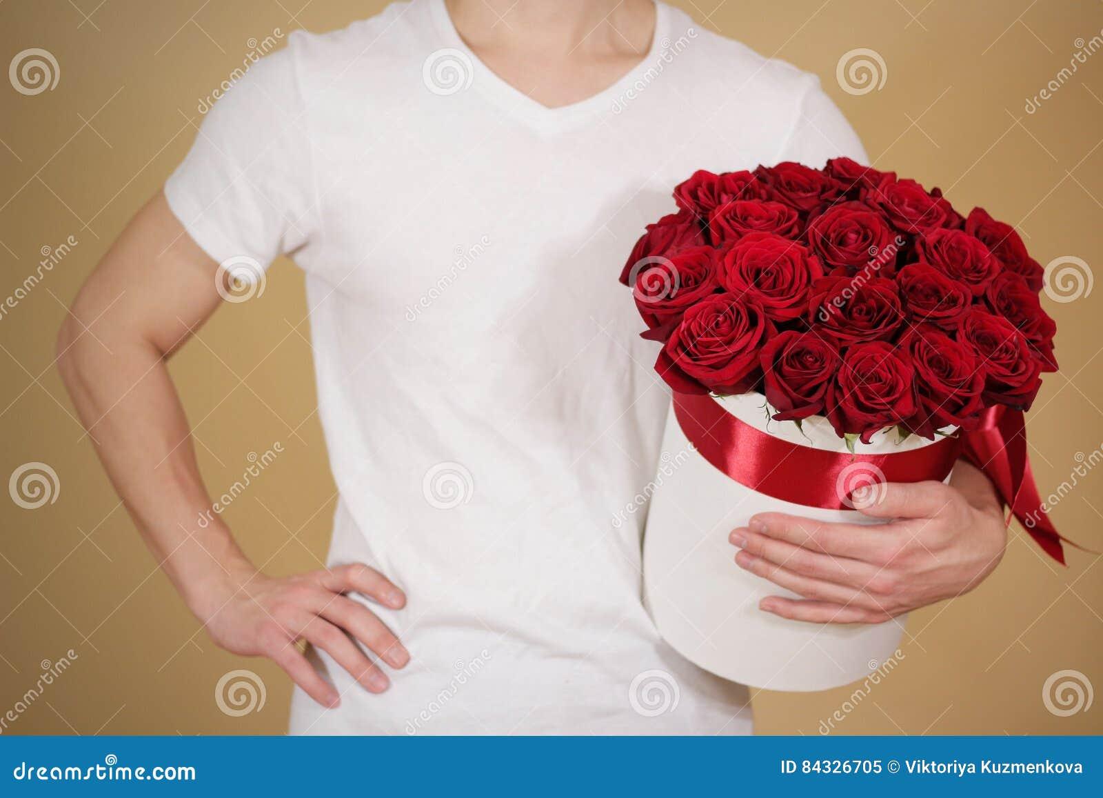 Man i det vita t-skjortainnehavet i rik gåvabukett för hand av röda 21
