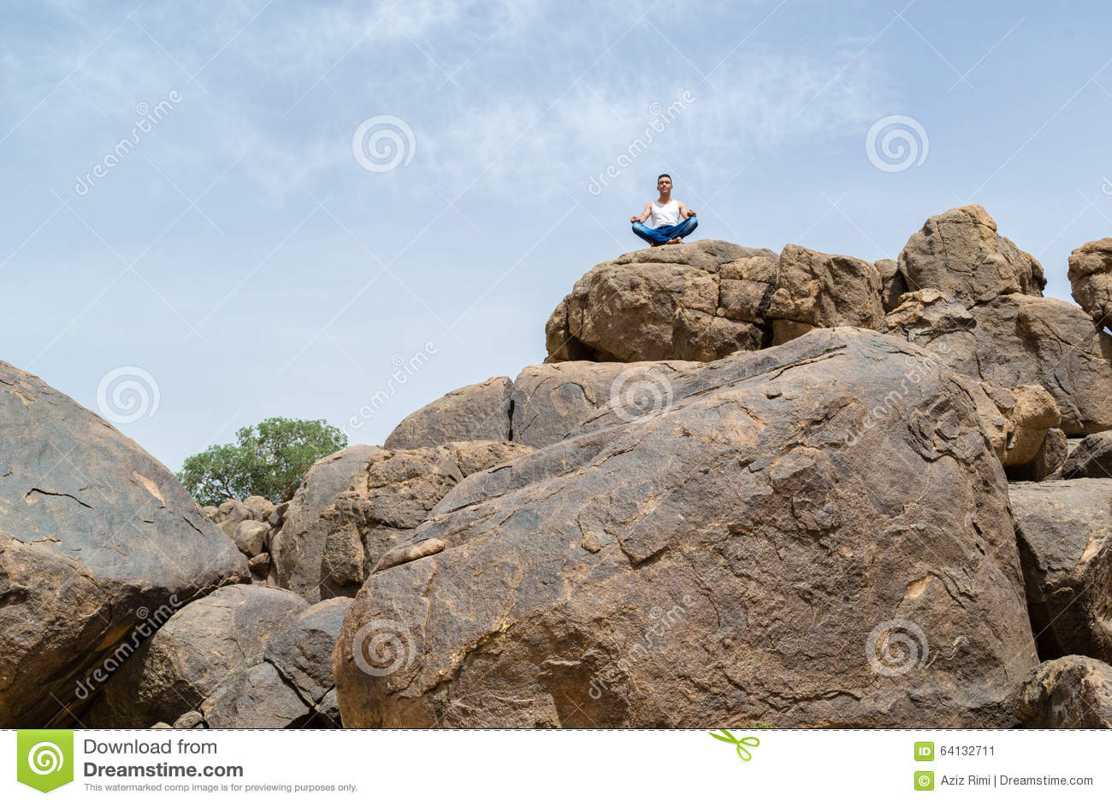 Man i djup yogakoncentration på ett stenigt berg - landskap