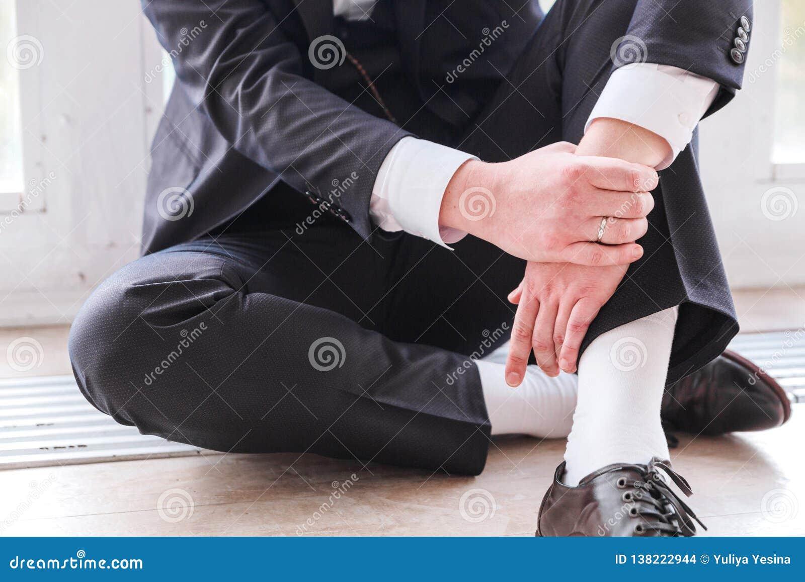 Man i en dräkt som sitter på golvet