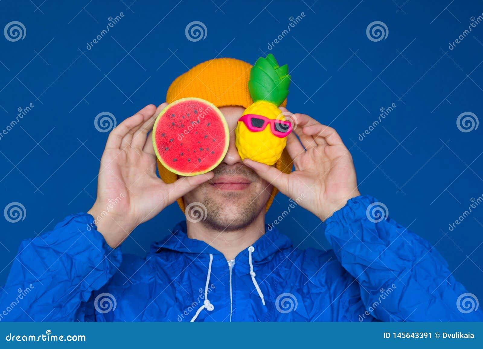 Man i ett blått omslag för sport90-talstil och en gul hatt med squishy vattenmelon- och ananasleksaker