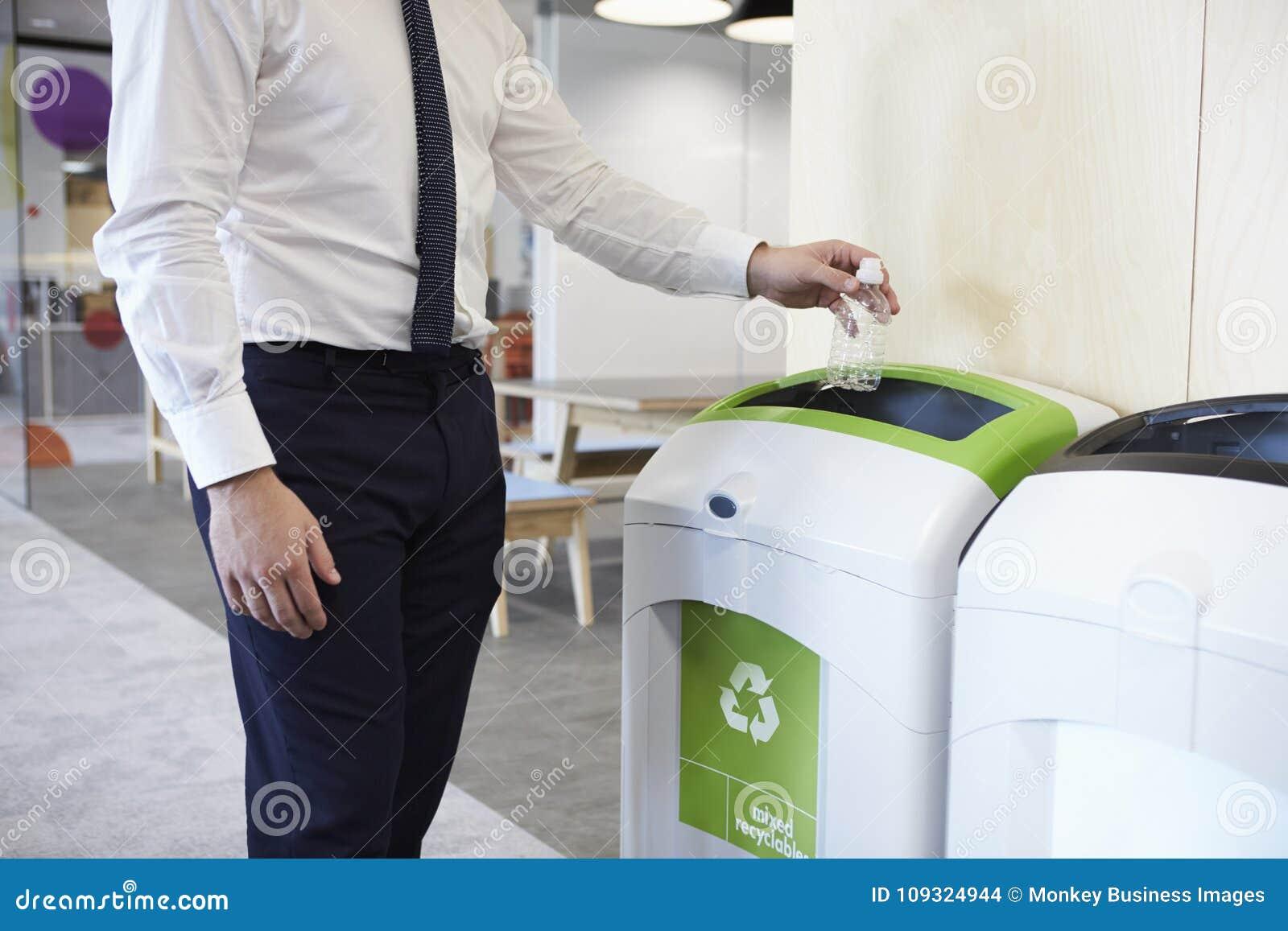 Man i ett kontor som kastar den plast- flaskan in i återvinningfack