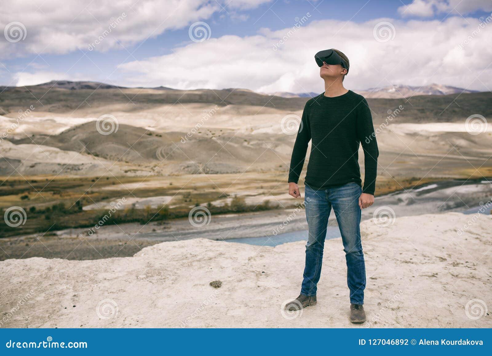 Man i exponeringsglas av virtuell verklighet mot bakgrunden av naturen