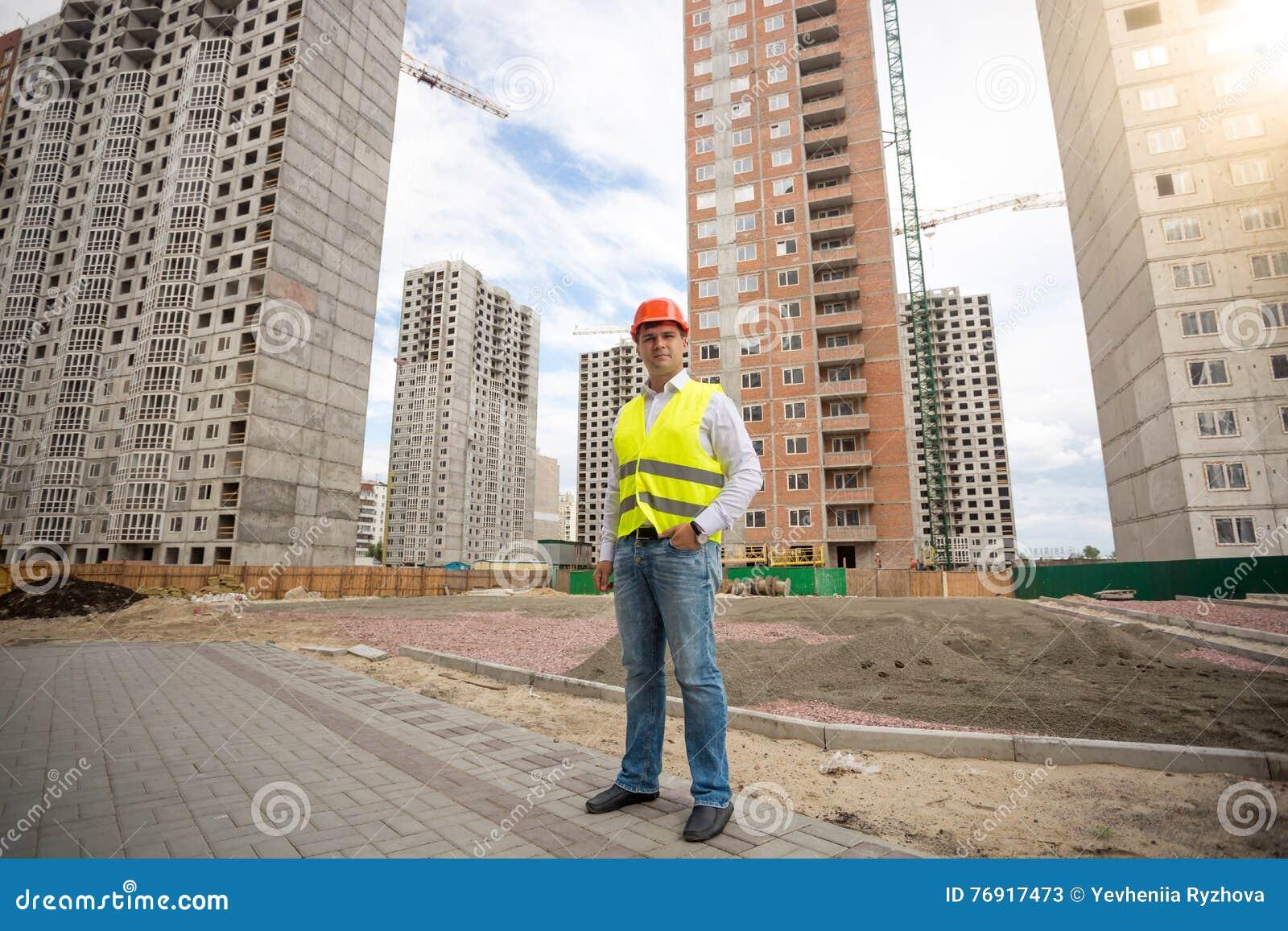 Man i hardhat- och säkerhetsvästanseende på byggnadsplats