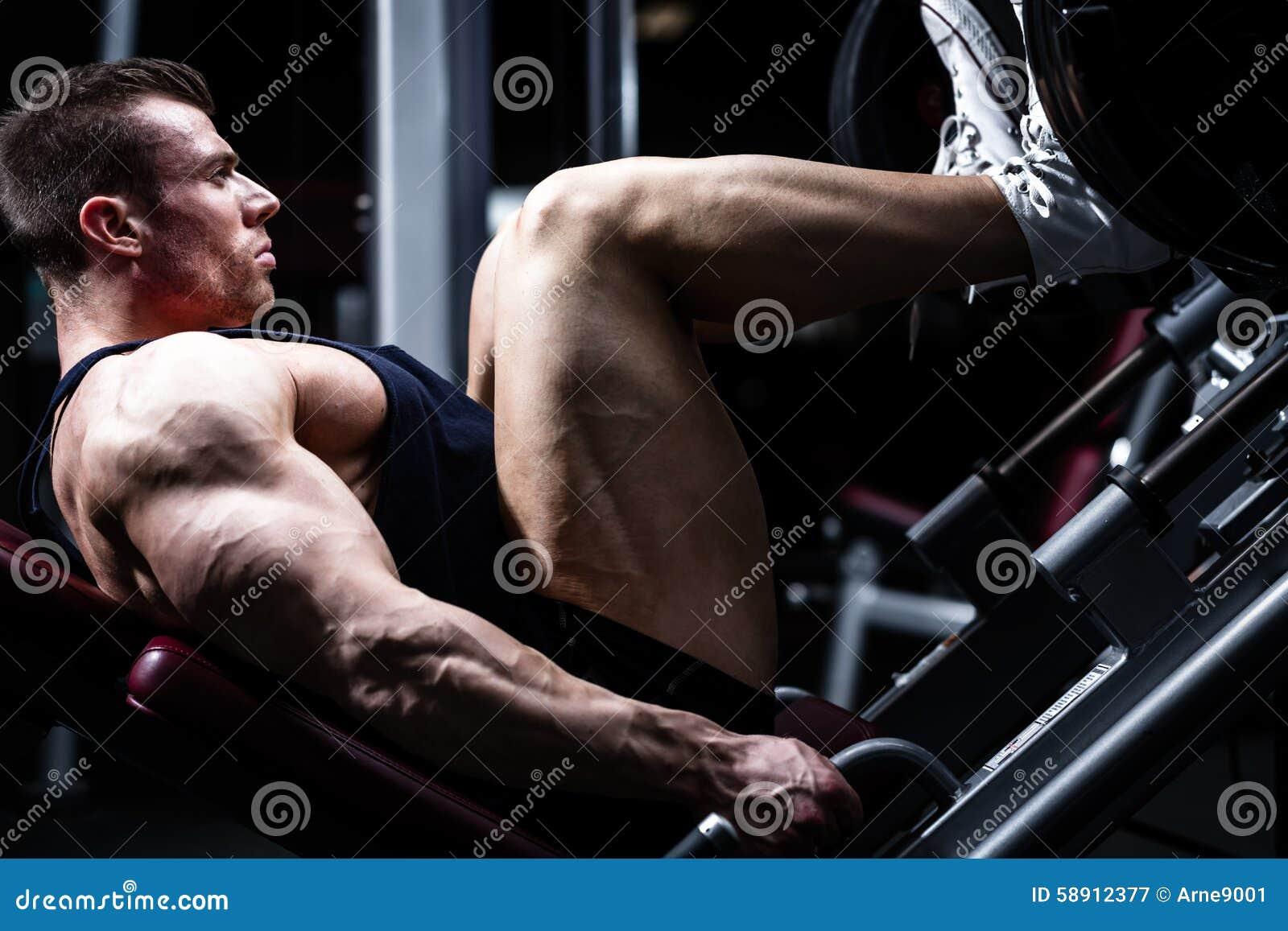 Man i idrottshallutbildning på benpress