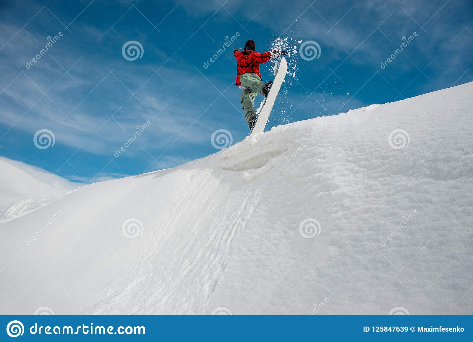 7953b8e9b588 Man in warm ski gear is jumping on a blue snowboard from a snowy mountain  against a blue sky and snow-capped mountain peaks