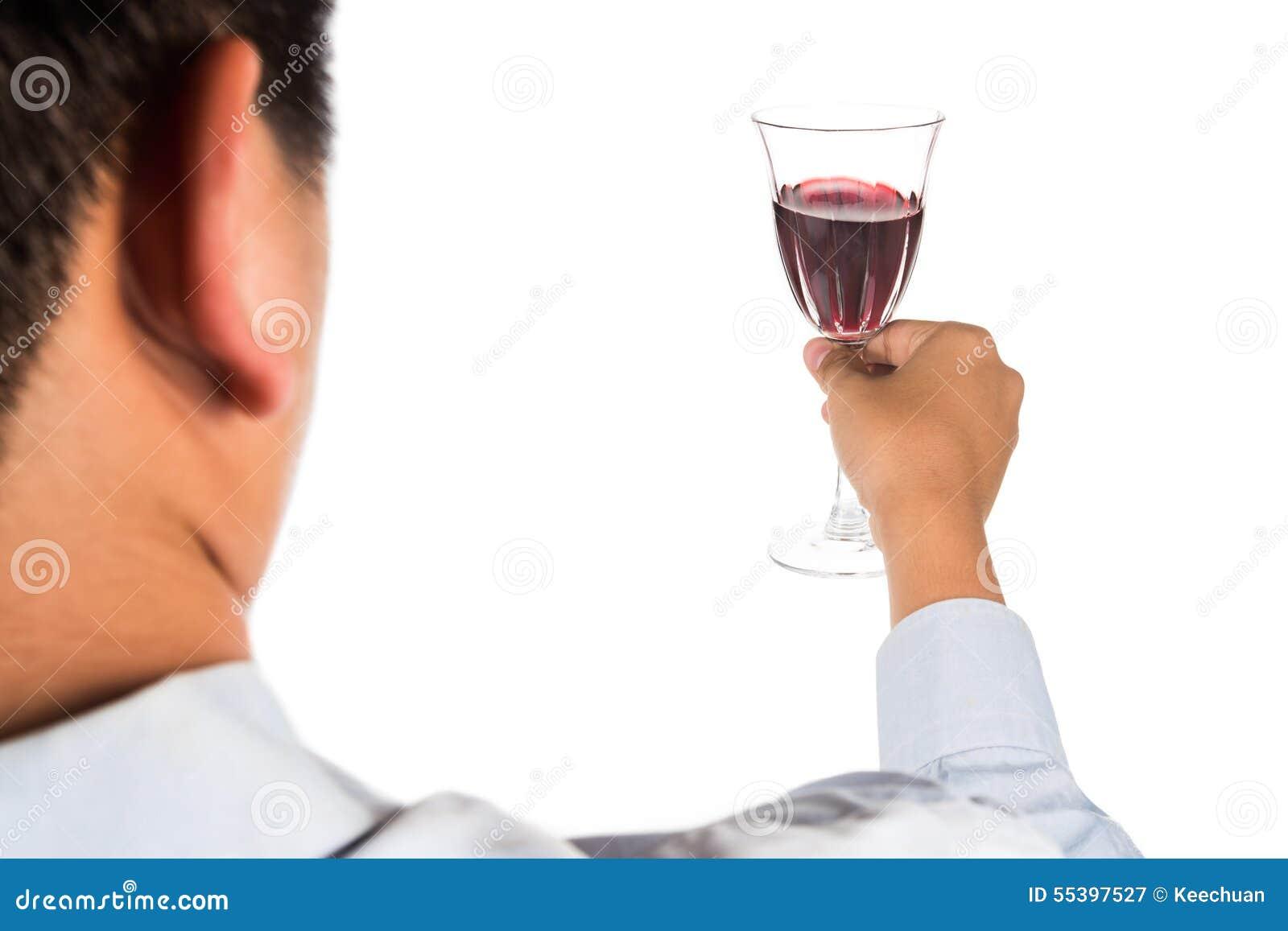 Man i lång muffskjorta som rostar rött vin i crystal exponeringsglas
