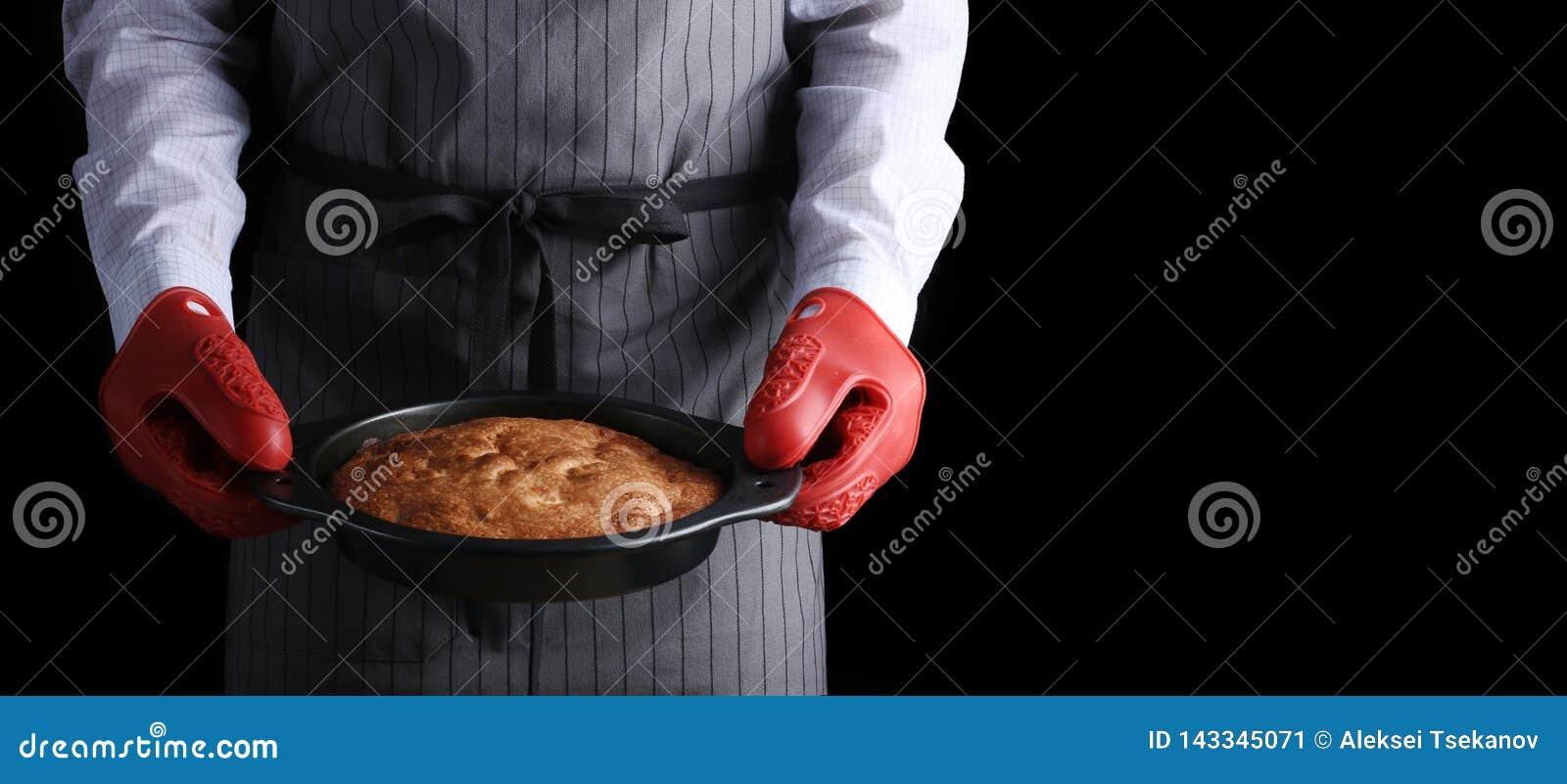 Man i mörk bakgrund för röd potholderinnehavpaj och som isolerar på svart receptbegrepp med ingredienser på tabellen